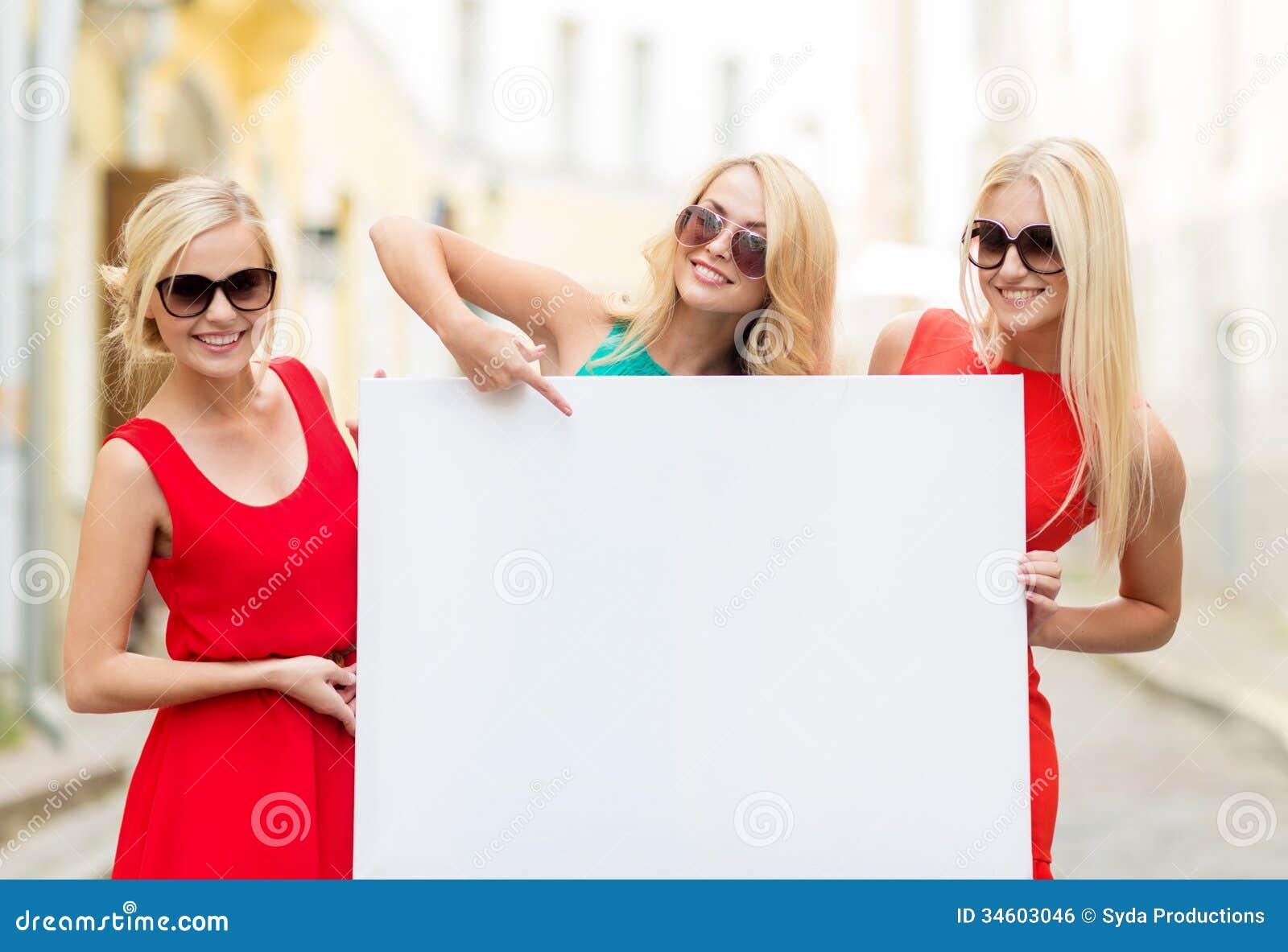 Trois femmes blondes heureuses avec le conseil blanc vide