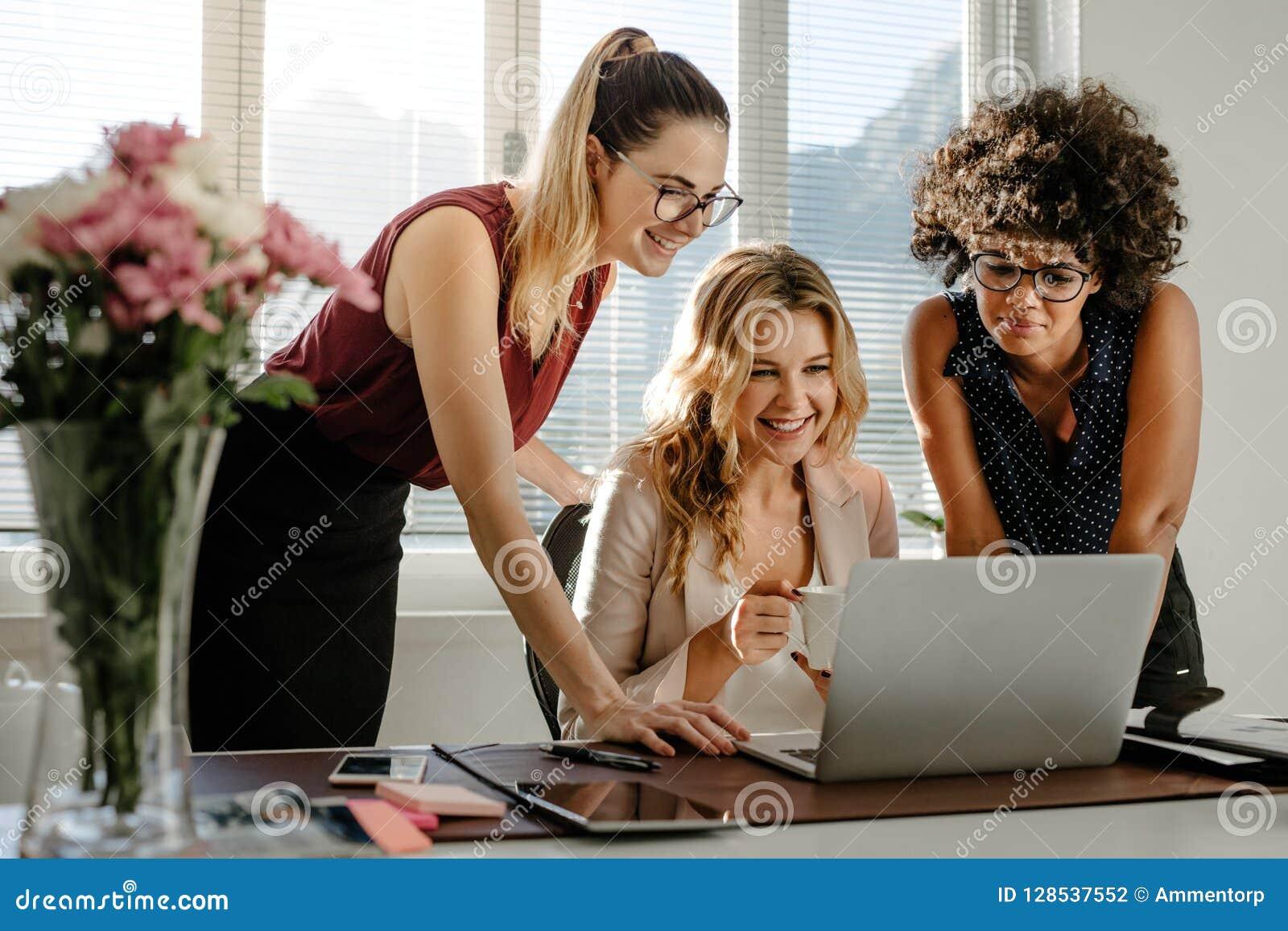 Trois femmes d affaires regardant l ordinateur portable et le sourire