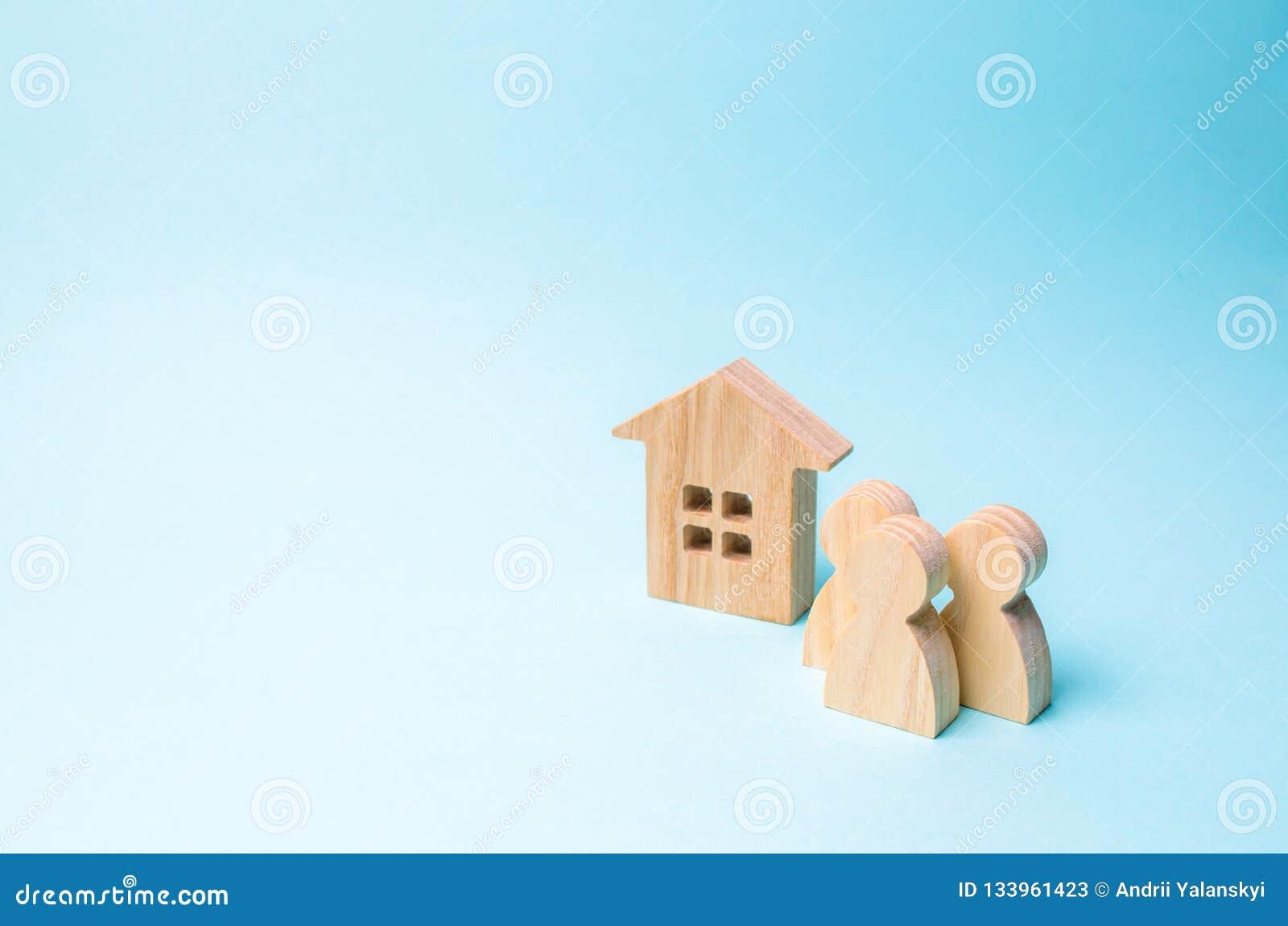 Trois figures des personnes et d une maison en bois sur un fond bleu Le concept du logement abordable et des hypothèques pour ach