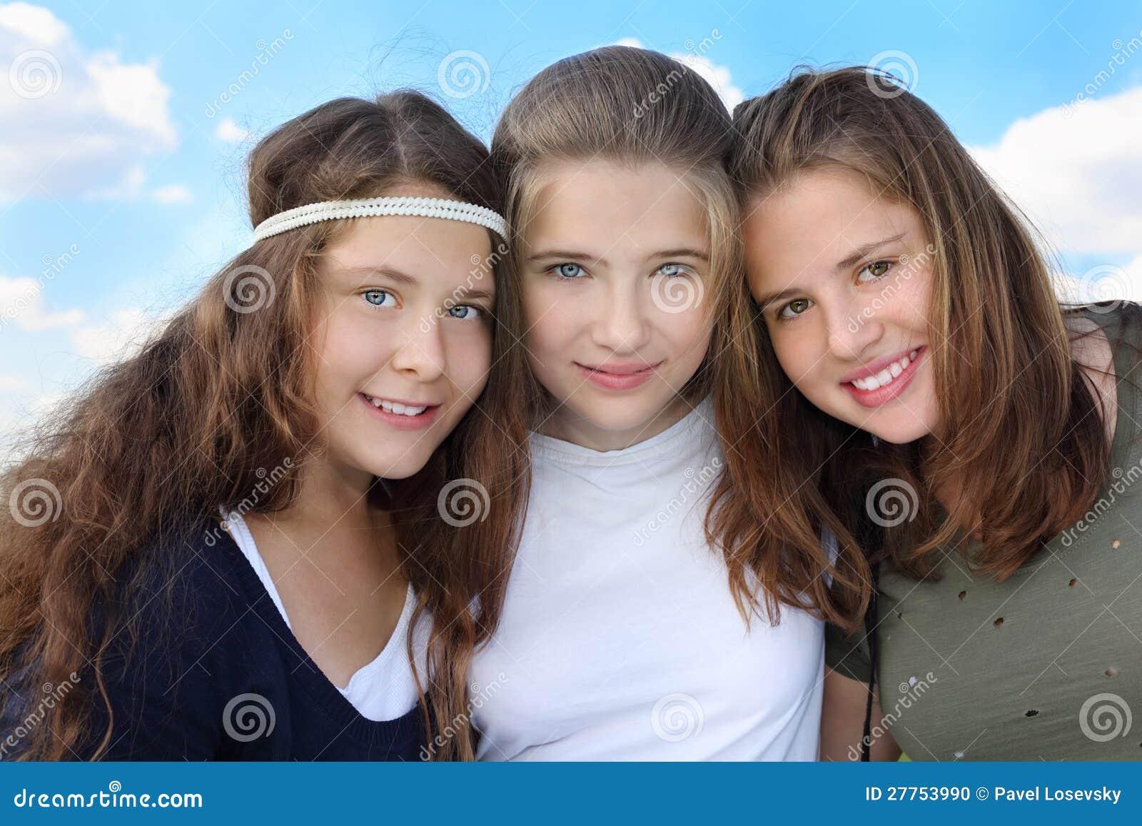 Trois filles de sourire étreignent au fond du ciel