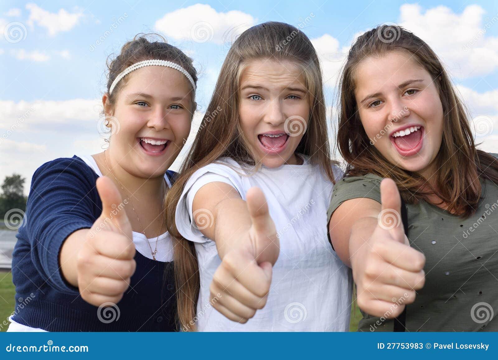 Trois filles heureuses crient et manient maladroitement vers le haut à l extérieur