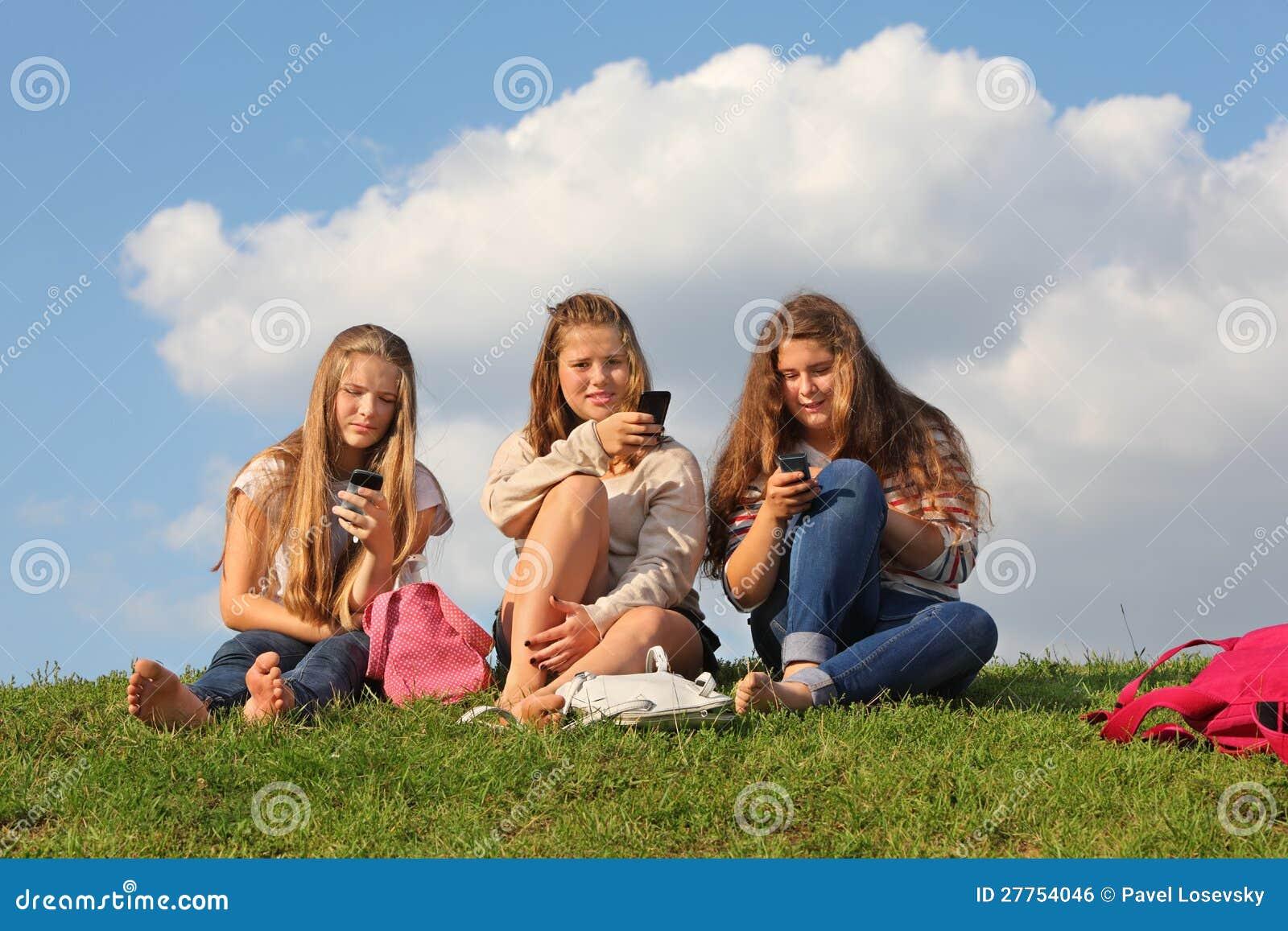 Trois filles s asseyent sur l herbe avec des téléphones portables