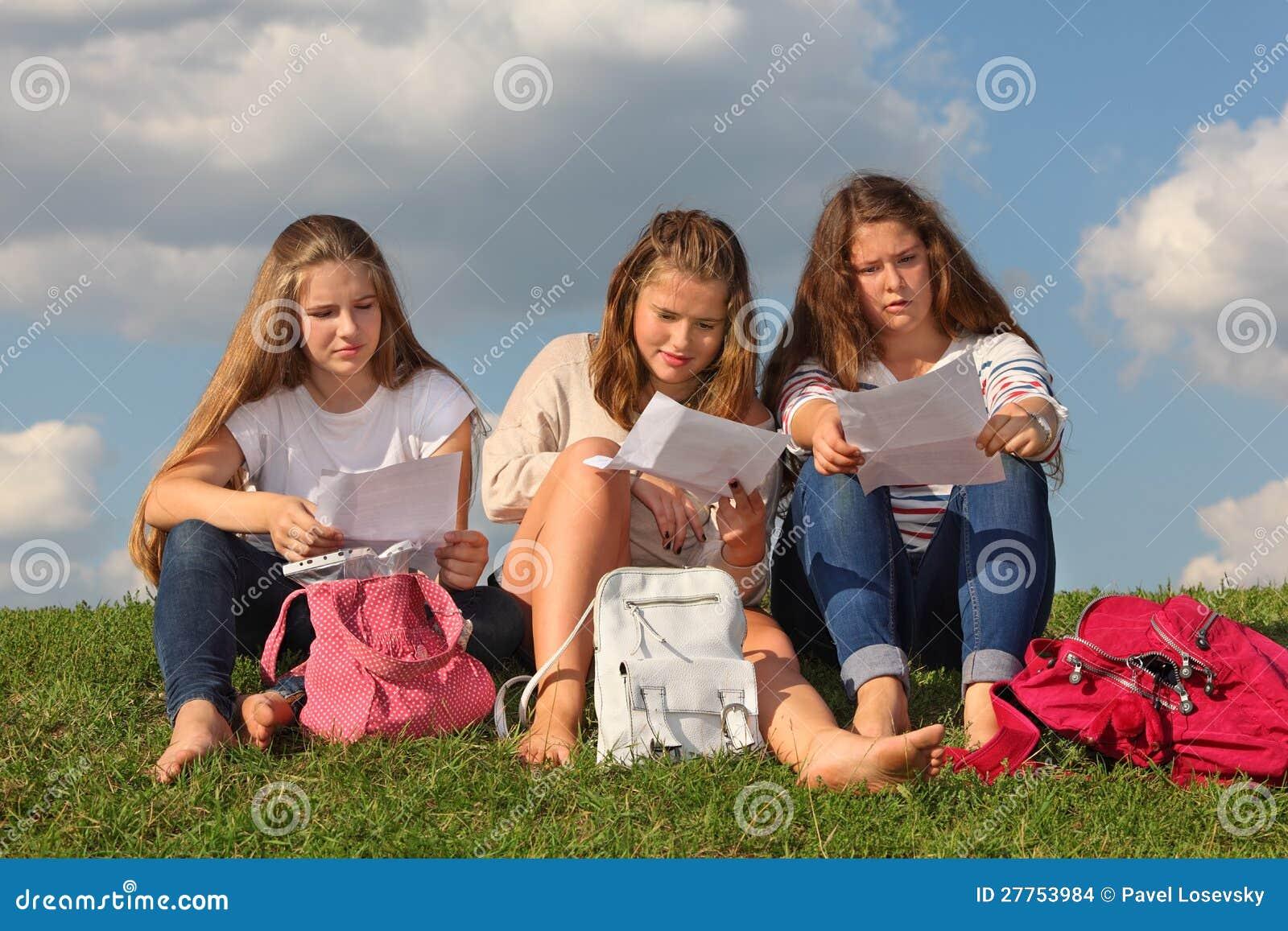 Trois filles s asseyent sur l herbe et affichent quelque chose