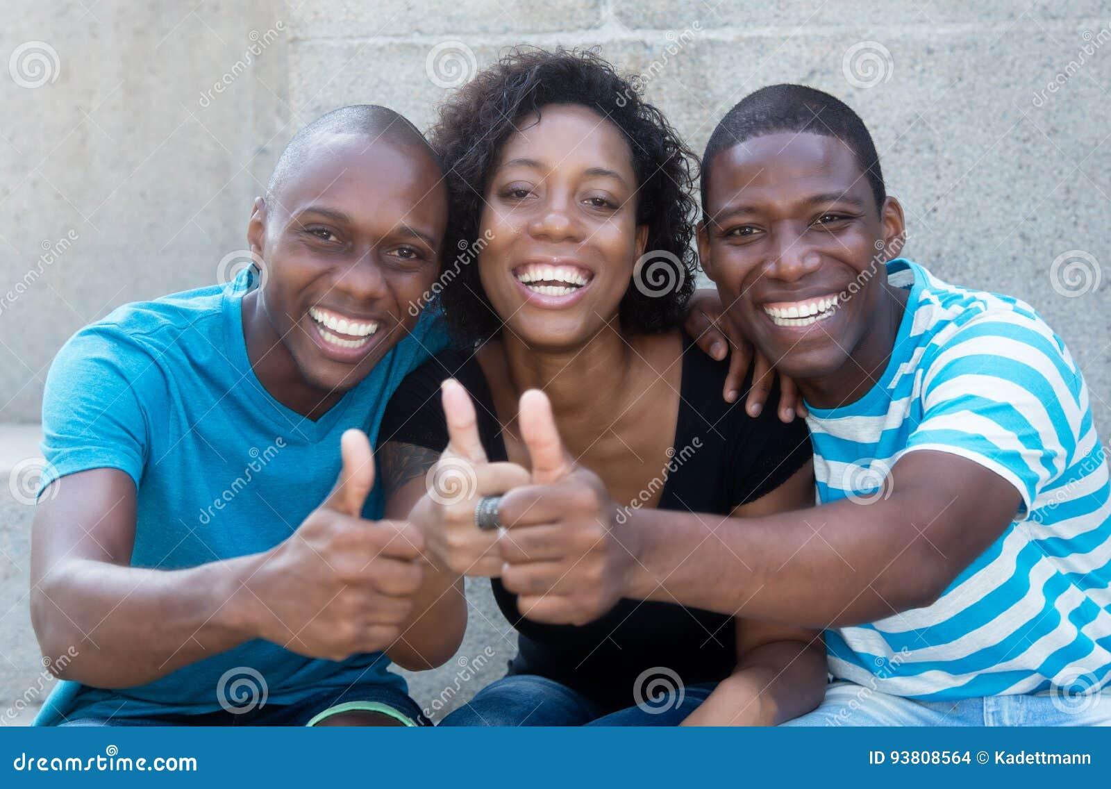 Trois hommes et femme d afro-américain montrant le pouce