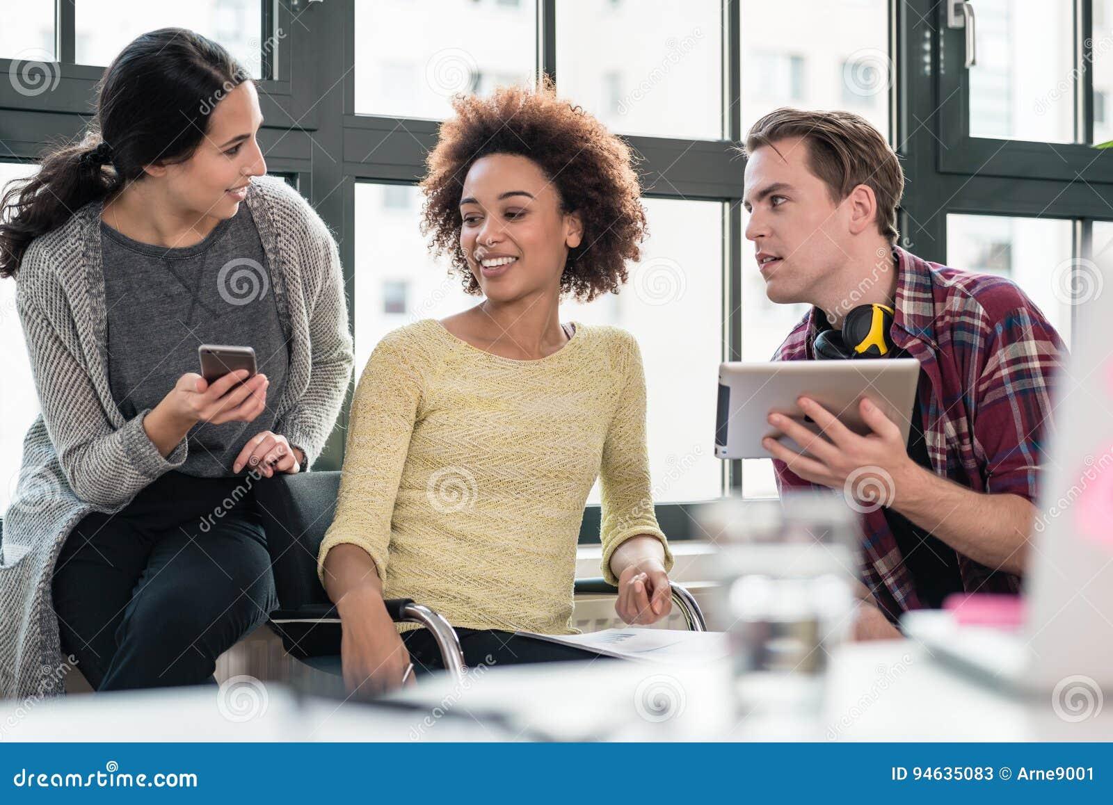 Trois jeunes employés à l aide des dispositifs modernes pendant la coupure