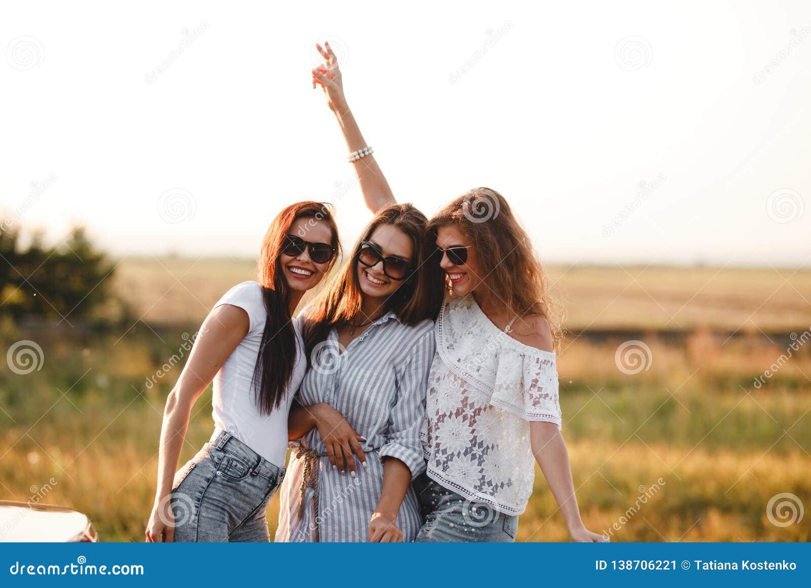 Trois jeunes femmes magnifiques dans des lunettes de soleil se tiennent dans le domaine et le sourire un jour ensoleillé