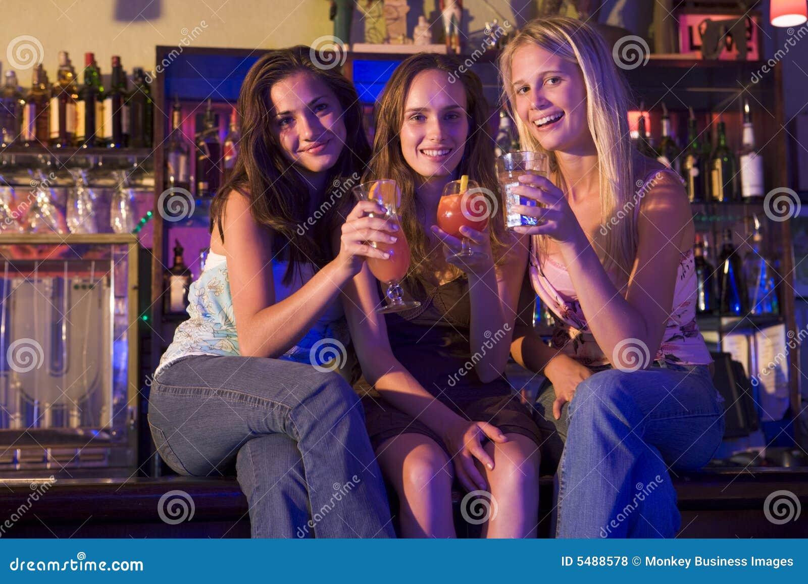 Trois jeunes femmes s asseyant sur un compteur de bar