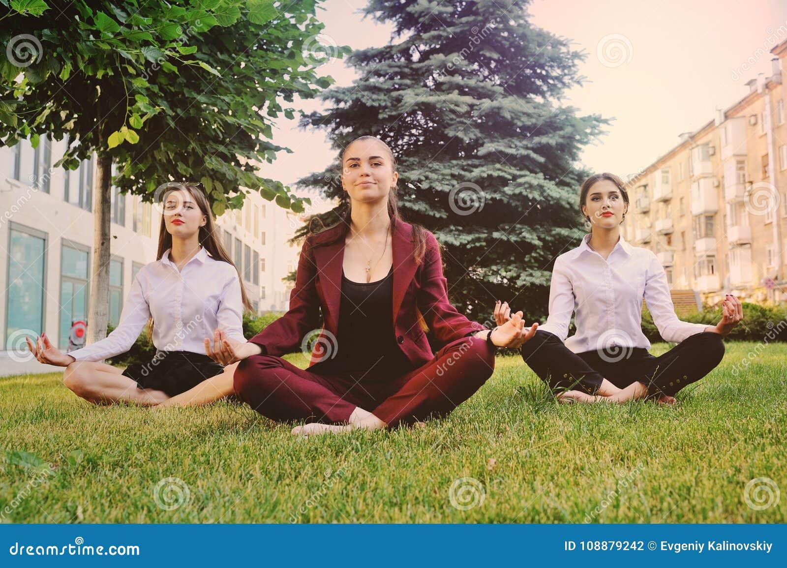 Trois jeunes filles habillées dans des vêtements de bureau pratiquent le yoga