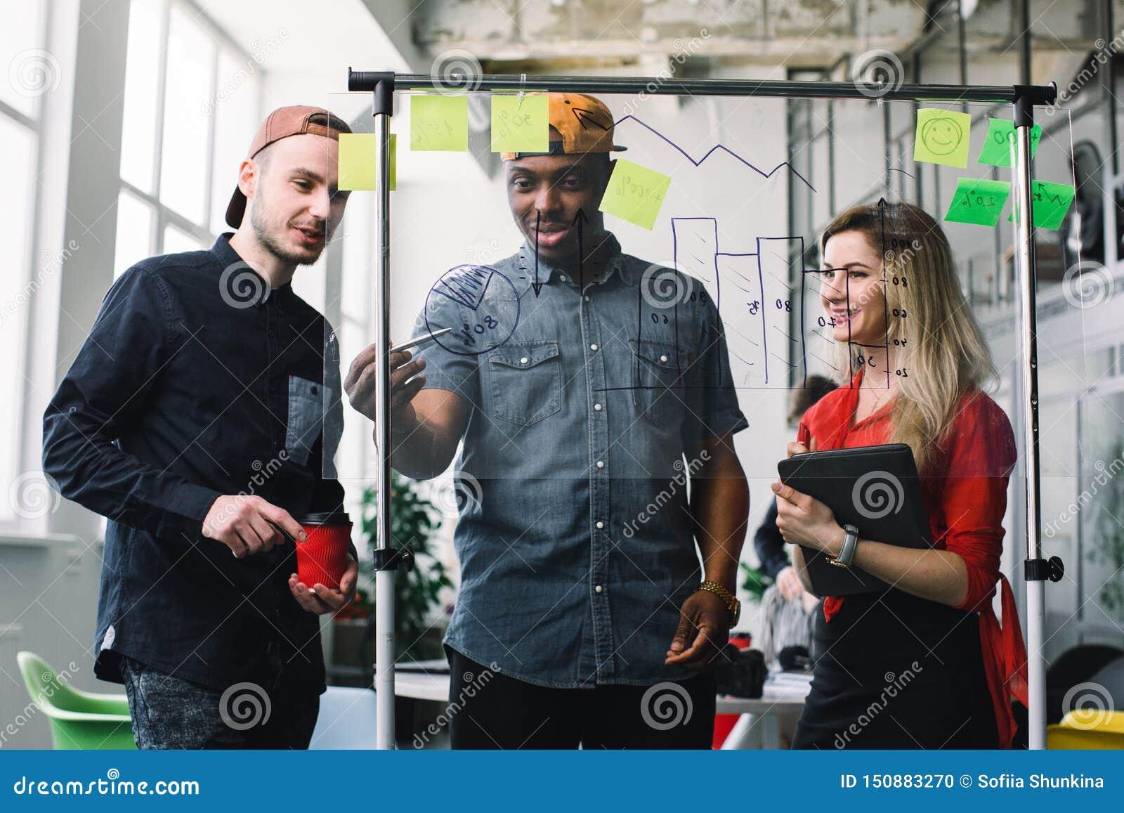 Trois jeunes hommes d affaires se réunissant aux notes de post-it de bureau et d utilisation pour partager l idée Concept de s?an