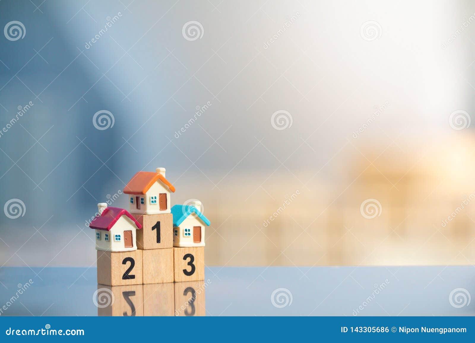 Trois maisons miniatures sur le premier endroit du podium de gagnant sur le fond moderne de ville