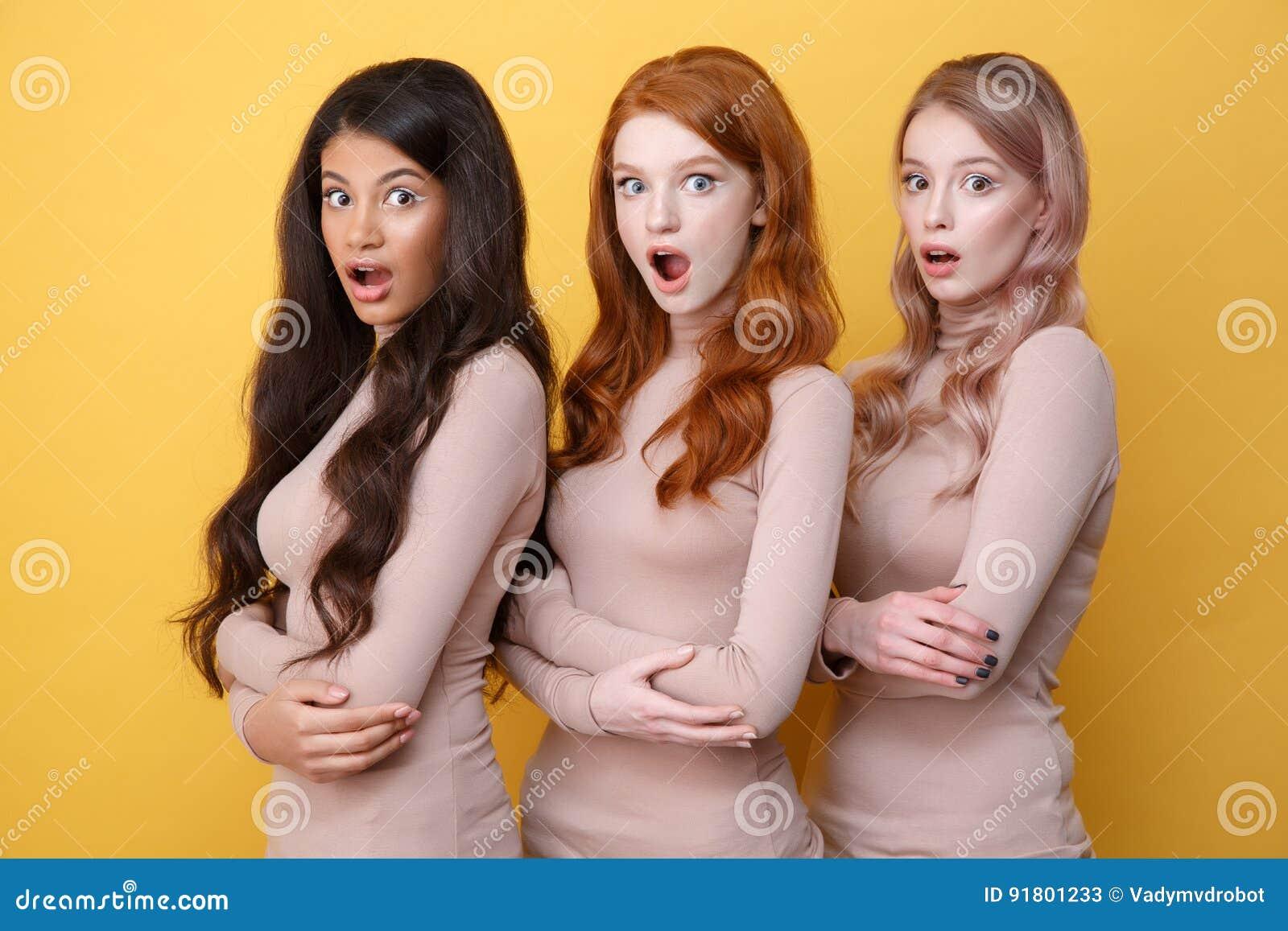 Trois ont choqué des dames avec les bras croisés posant dans le studio