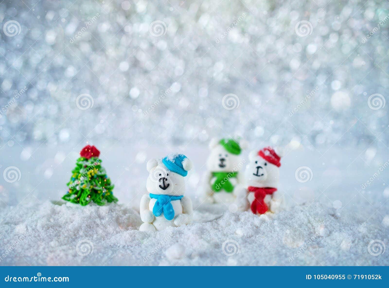 Trois ours de sucrerie de sucre dans la neige sur le fond de bokeh avec l espace de copie pendant Noël ou la bonne année de salut
