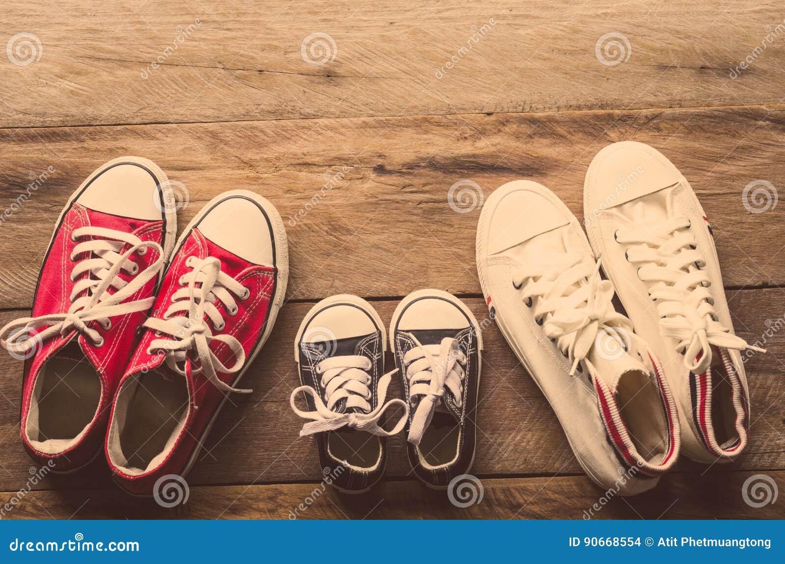 Trois paires de chaussures s étendent sur le plancher en bois de la famille, des parents et des enfants pour faire ensemble