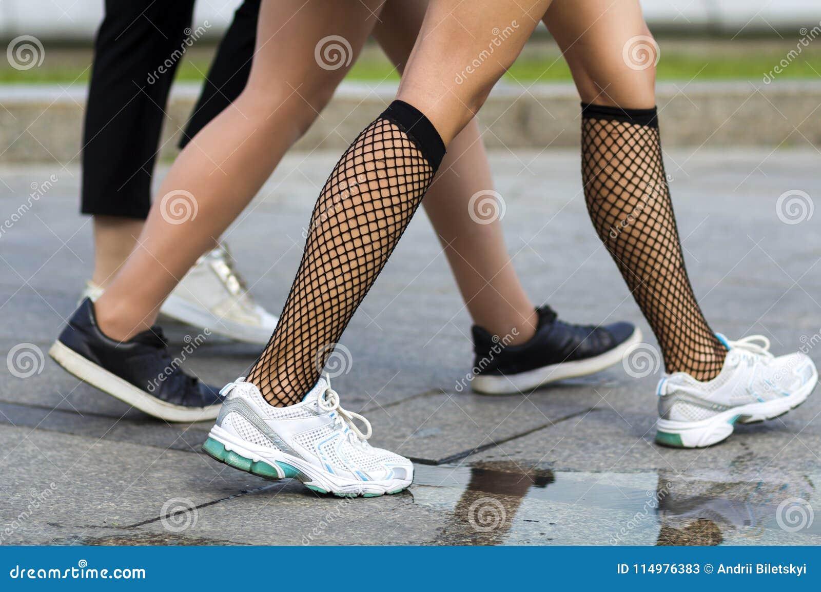 Trois paires de jambes minces de jeunes filles d ajustement dans le sport différent chausse la marche rapidement le long de la ro