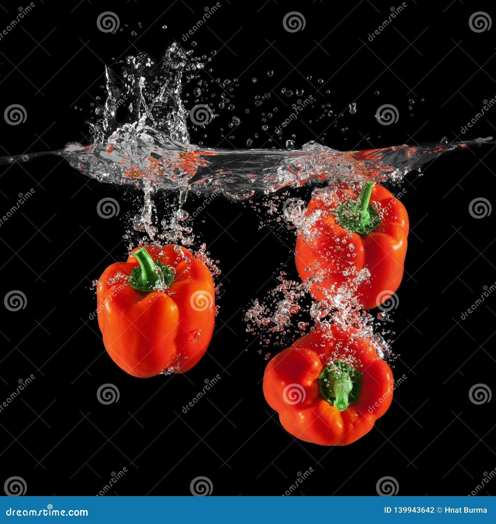 Trois paprikas rouges tombant dans l eau avec l éclaboussure sur le fond noir, paprika, arrêtent la photographie de mouvement