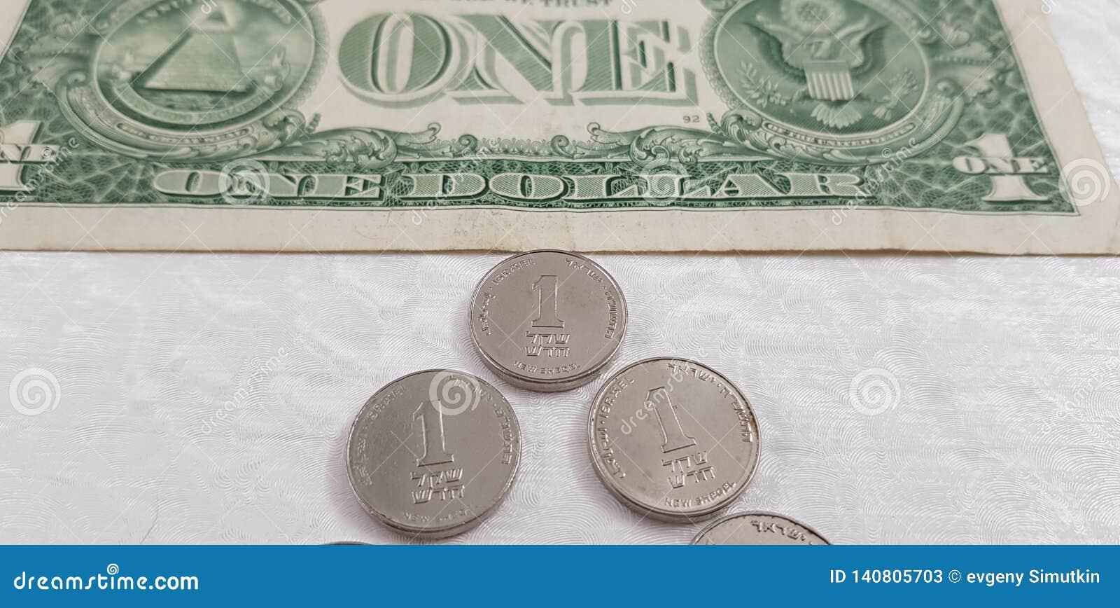 Trois pièces de monnaie israéliennes de sheckel sur le fond blanc près du billet de banque américain du dollar