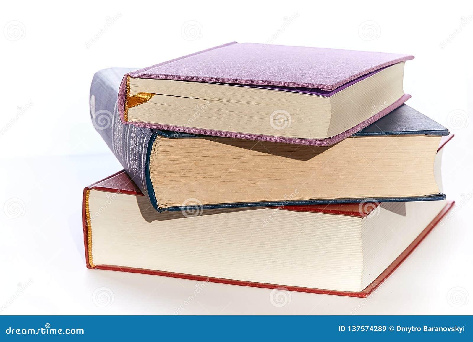 Trois plans rapprochés de livres de différentes couleurs se trouvent sur l un l autre Blanc de fond