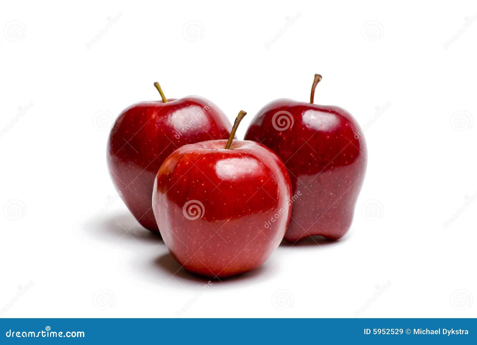 Trois pommes rouges sur le blanc