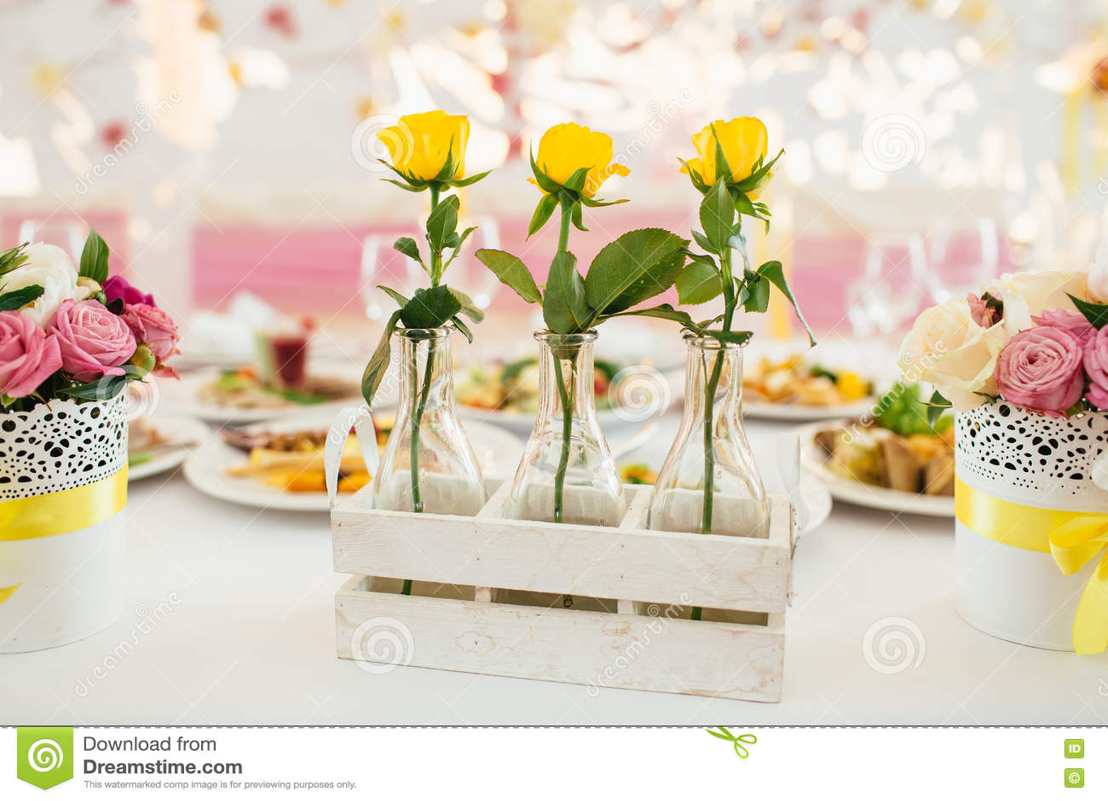 Trois roses de tellow en verre vasen sur la table décorée par fantaisie