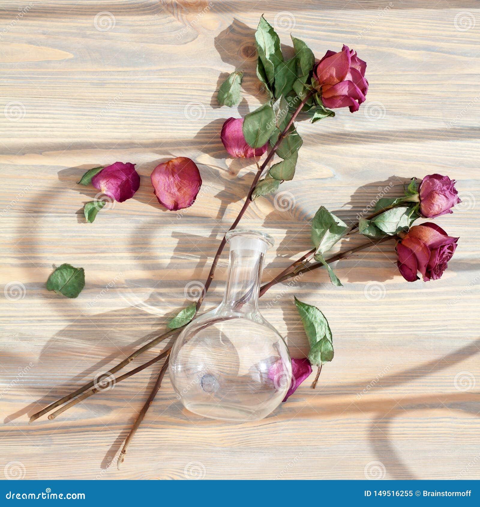 Trois roses rouges, p?tales dispers?s de fleur, feuilles vertes, vase rond en verre sur le plan rapproch? en bois de vue sup?rieu