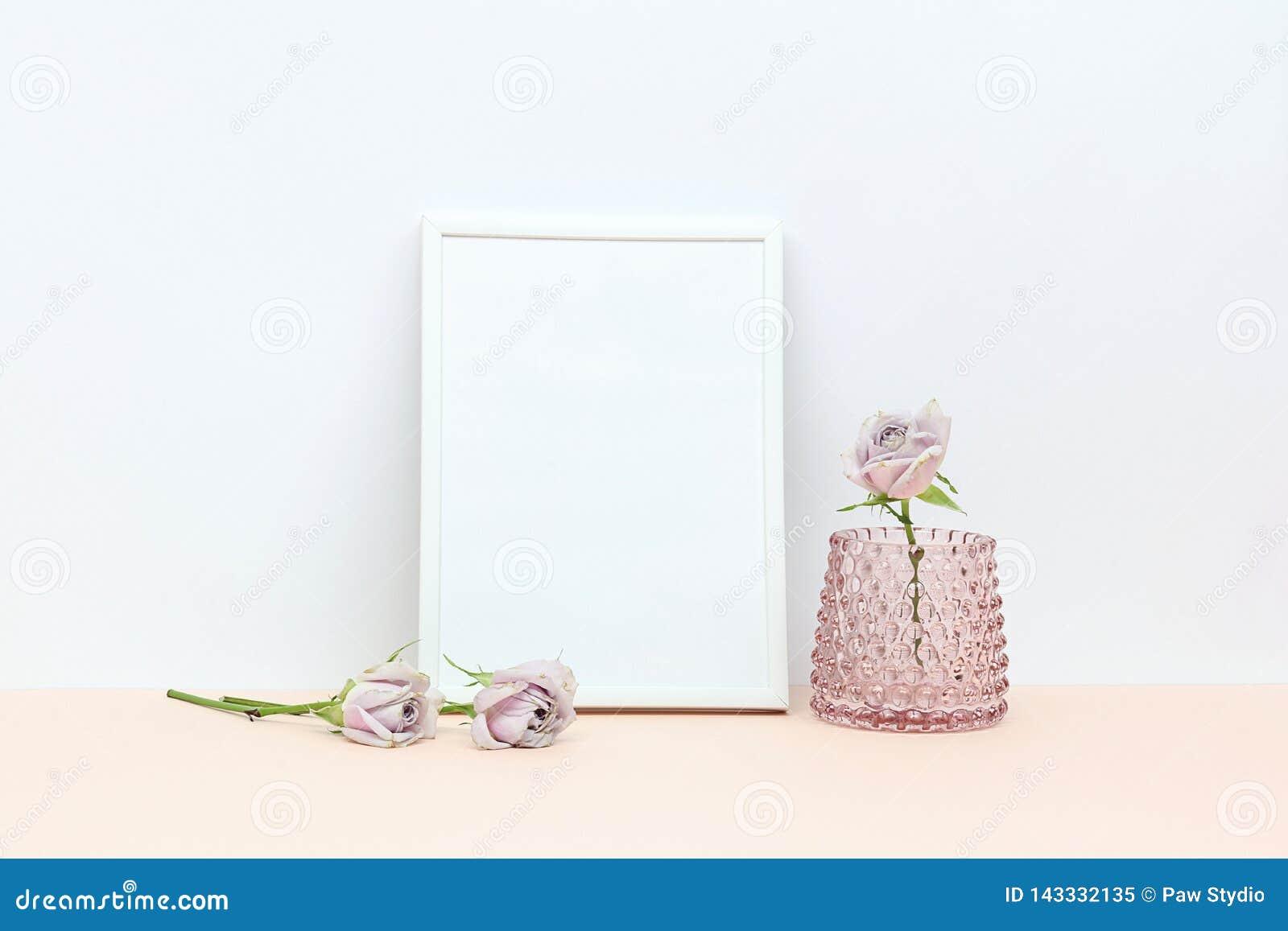 Trois roses roses sur le bureau et le cadre blanc