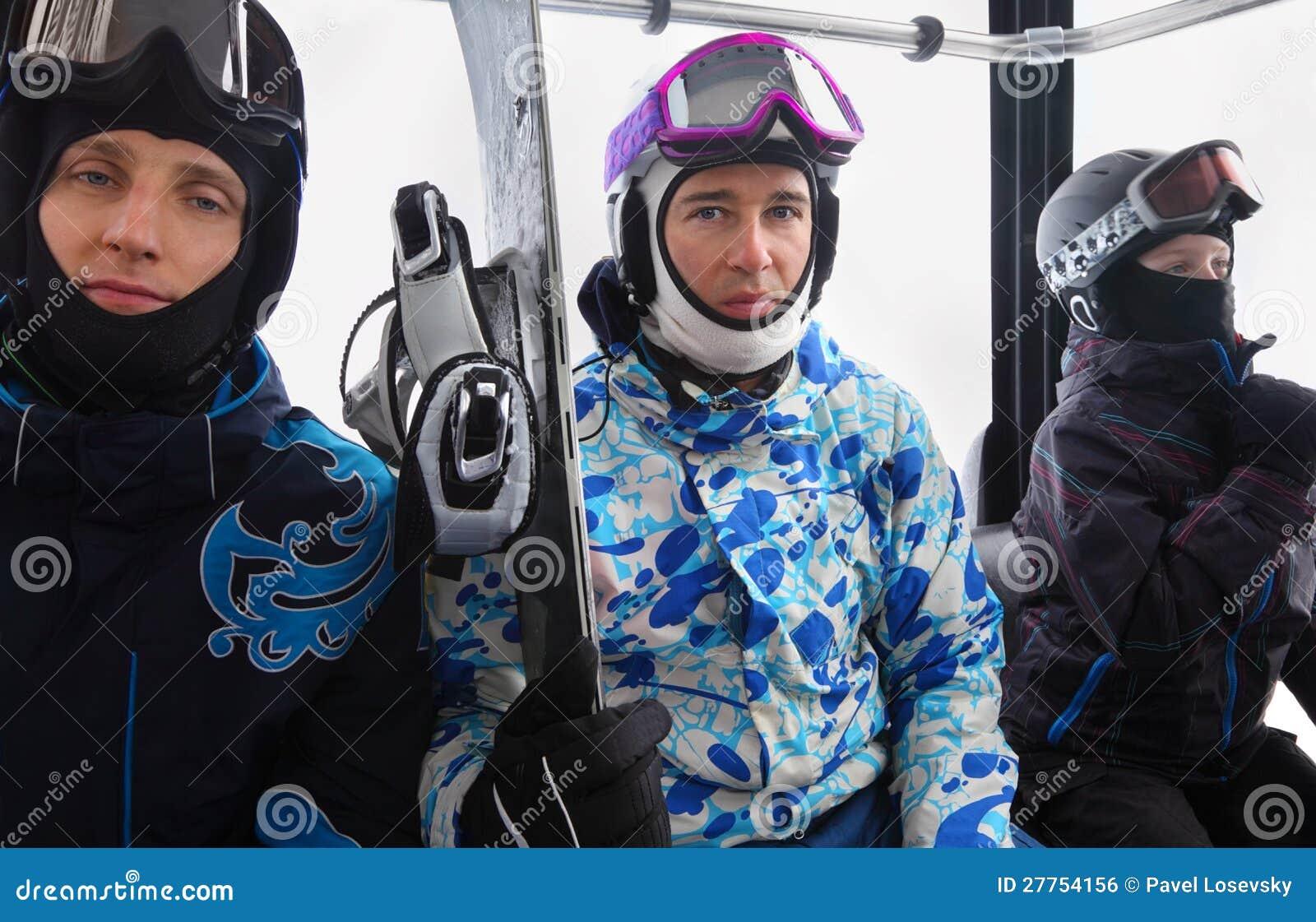 Trois skieurs dans la conduite de casques sur funiculaire
