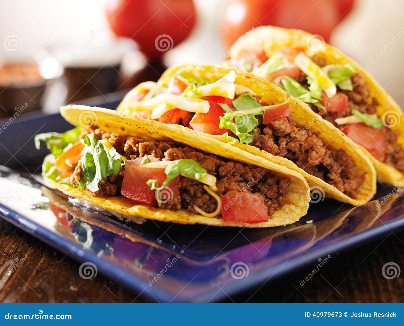 Trois tacos de boeuf avec du fromage, la laitue et des tomates