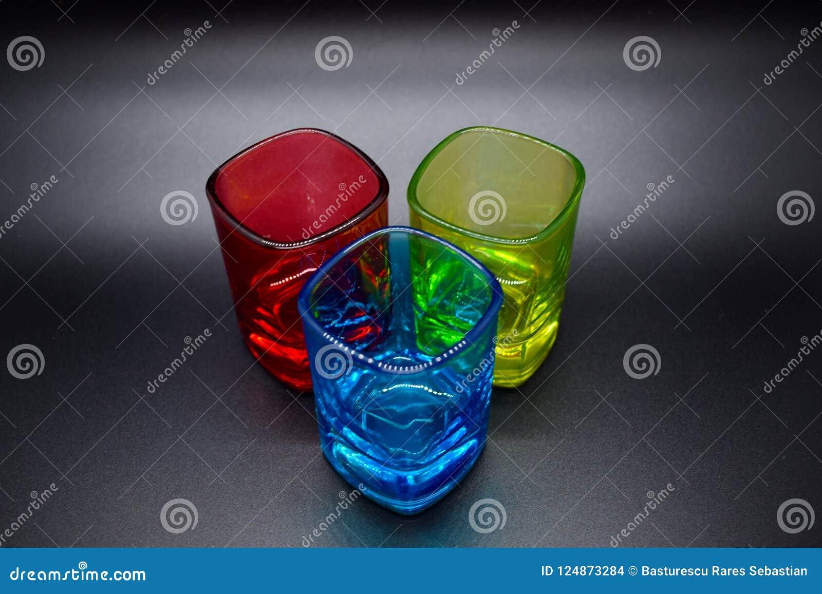 Trois verres à liqueur multicolores sur le fond noir