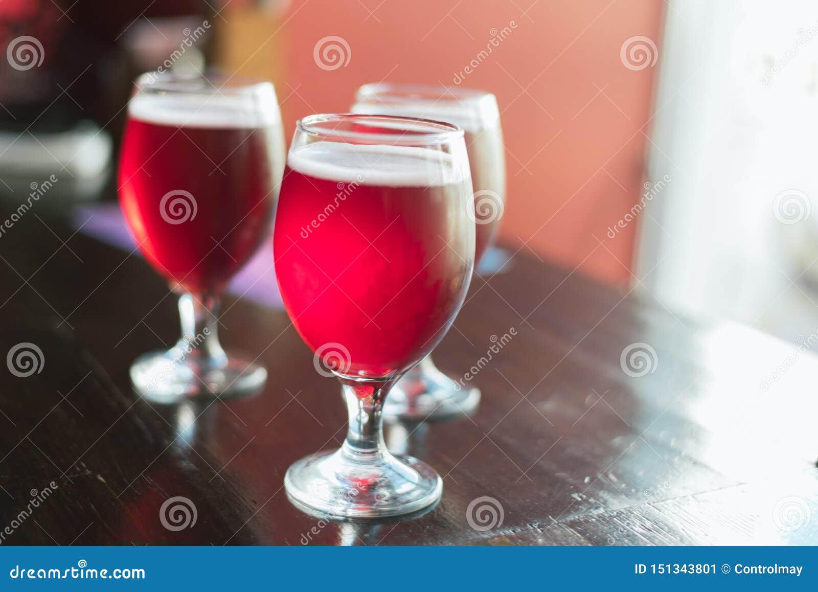 Trois verres avec le vin rouge sur une table en bois Les verres de bière de cerise sont sur la table Il n y a personne dans le ca