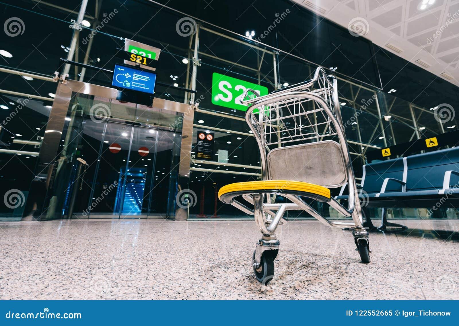 Trole do carro da bagagem na porta moderna do aeroporto