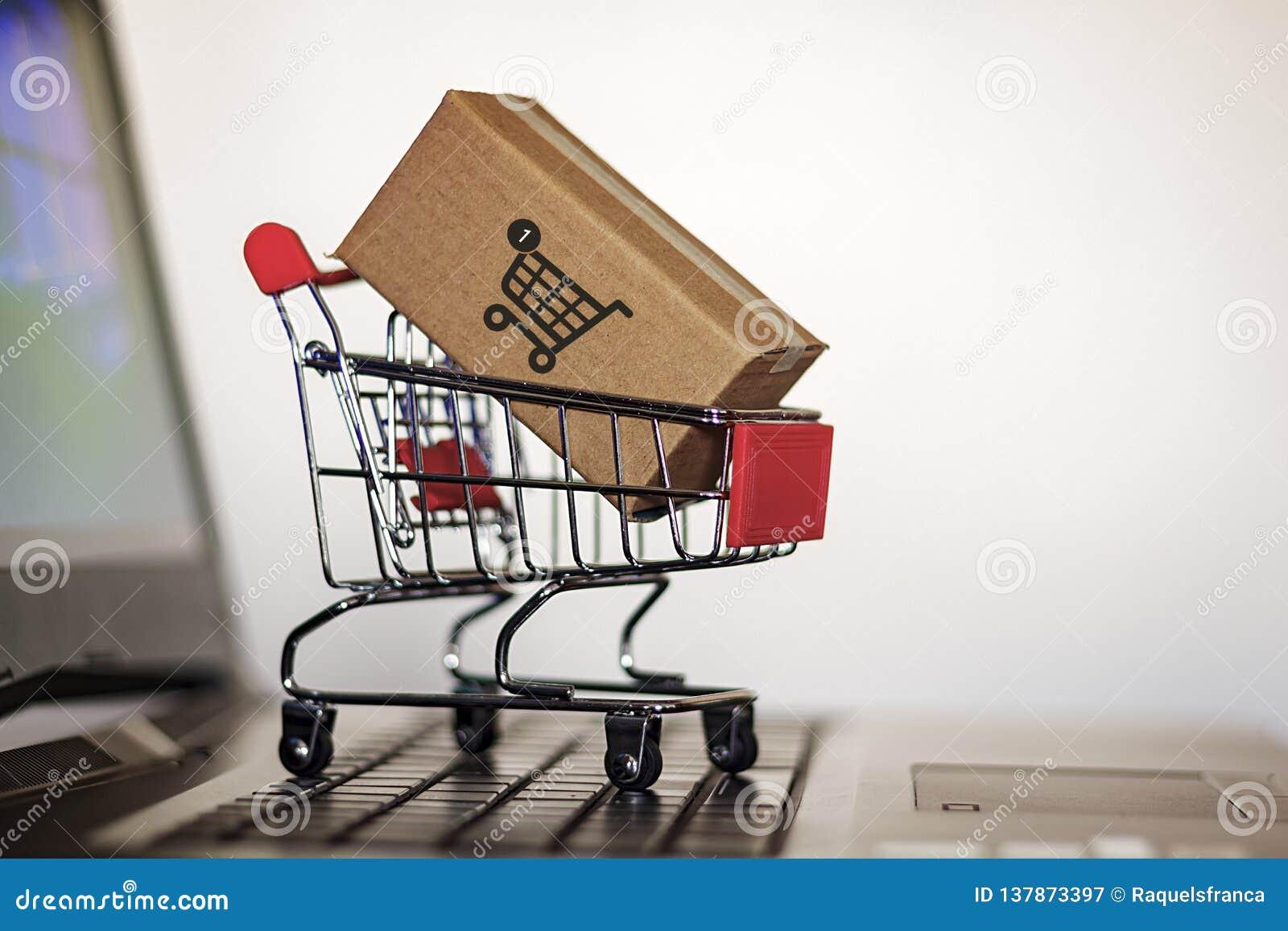 Troley с коробкой на клавиатуре компьютера Онлайн покупки, электронная коммерция и всемирная грузя концепция
