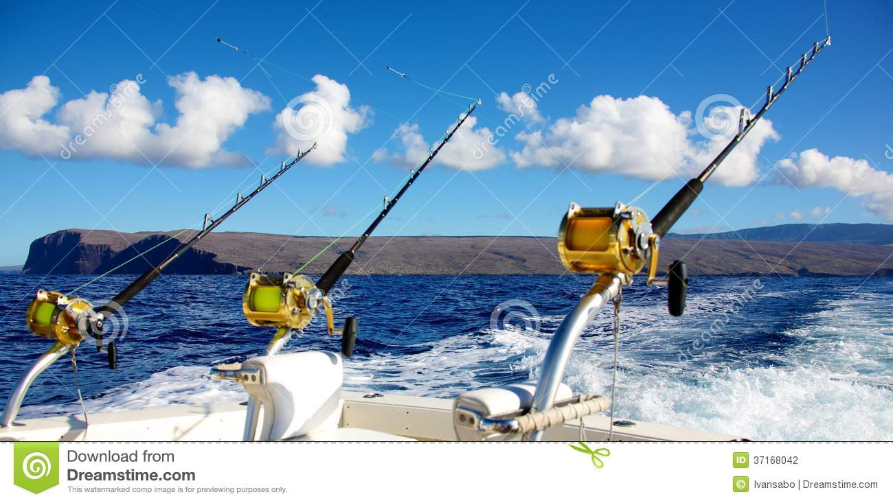 Deep sea fishing rods and reels trolling behind a fishing boat in the ...