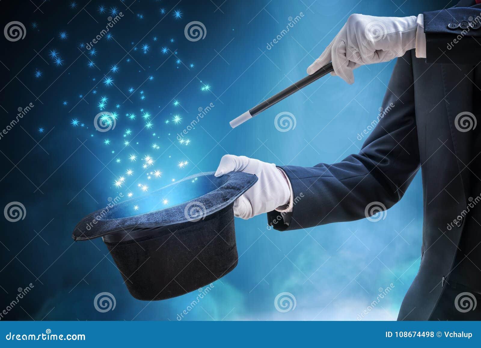 Trollkarlen eller illusionisten visar magiskt trick Blått etappljus i bakgrund