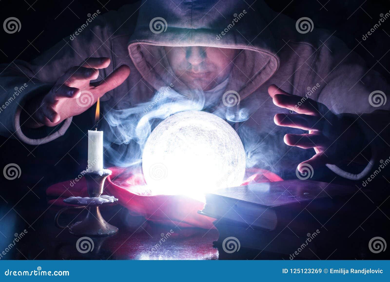 Trollkarlen med huven och ljus röker magisk kristallkula