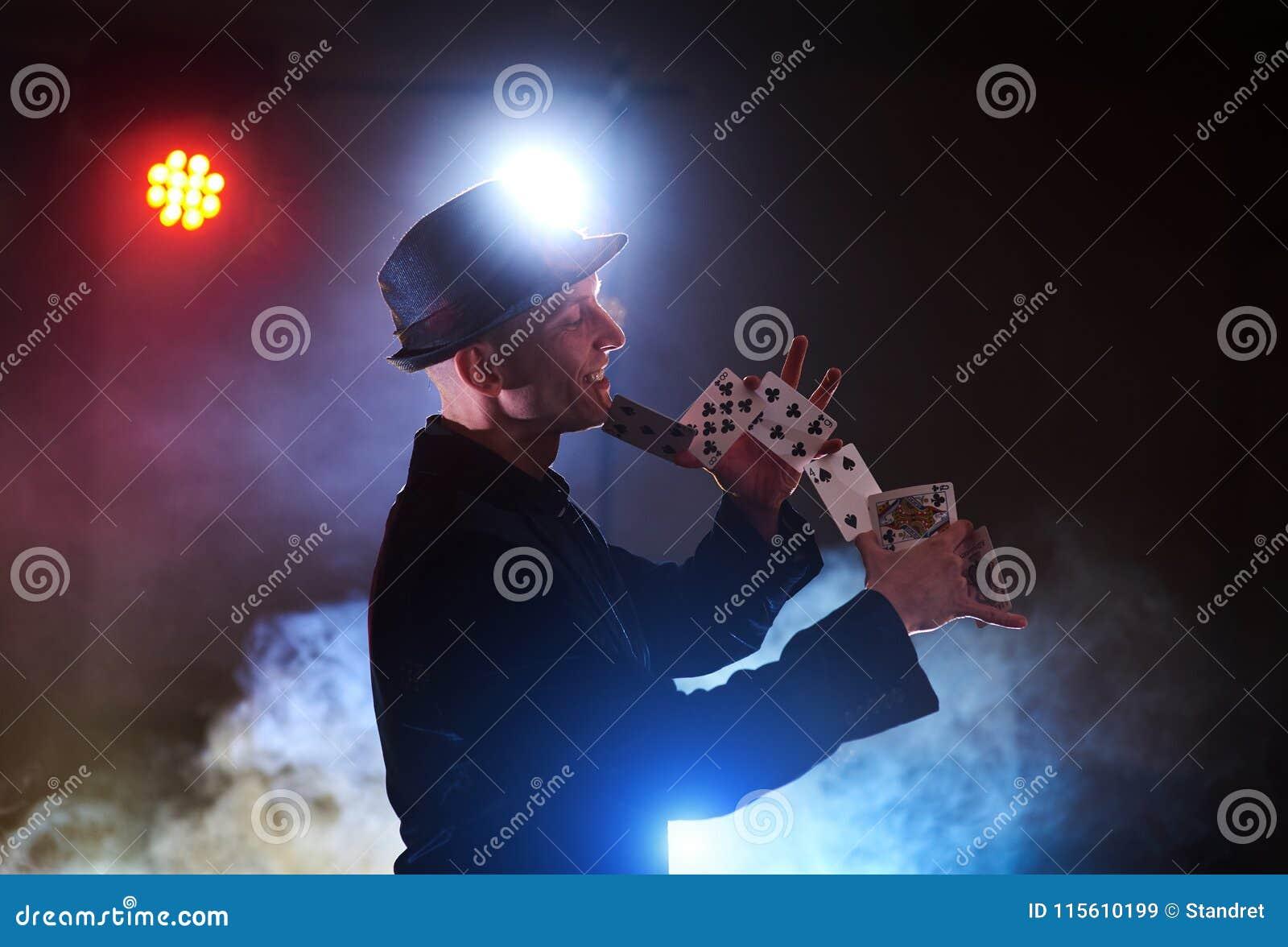 Trollkarlvisningtrick med att spela kort Magi eller skicklighet, cirkus som spelar Taskspelare i mörkt rum med dimma