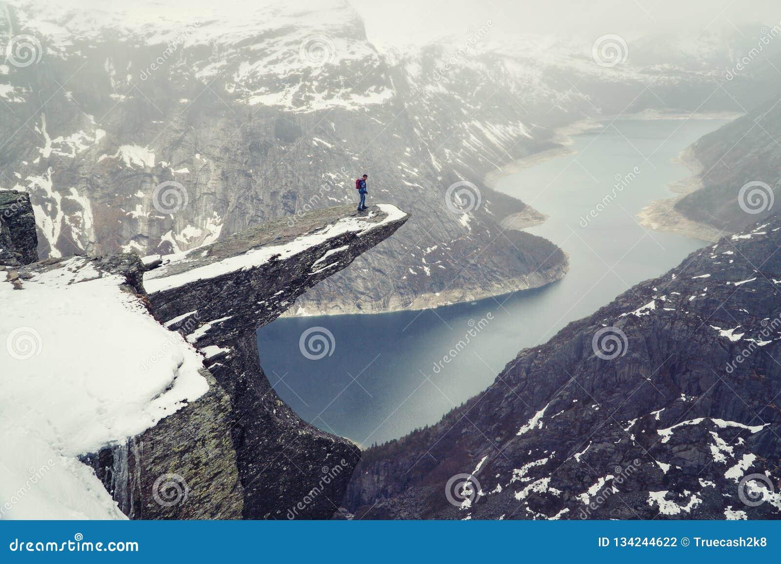 Trolltunga klippa under insnöade Norge scenisk liggande Manhandelsresandeanseendet på kanten av vaggar och se ner Resor