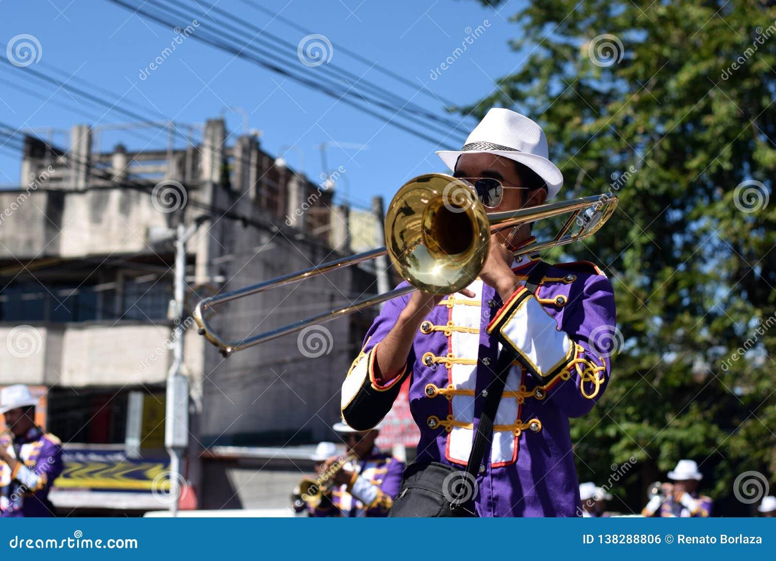 Trompette masculine de jeu de membre du groupe pendant le cortège de festivité de ville