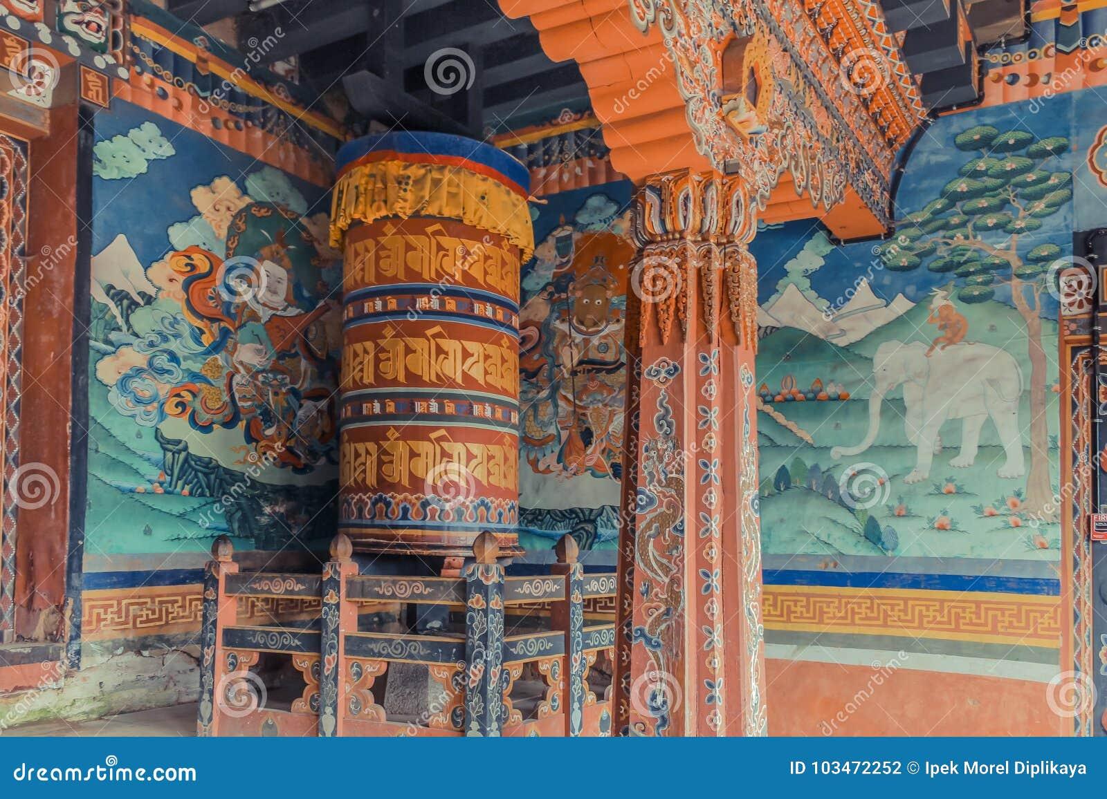 Trongsa, Bhután - 13 de septiembre de 2016: Pinturas de pared y rueda de rezo grande dentro del pórtico del Trongsa Dzong, Bhután