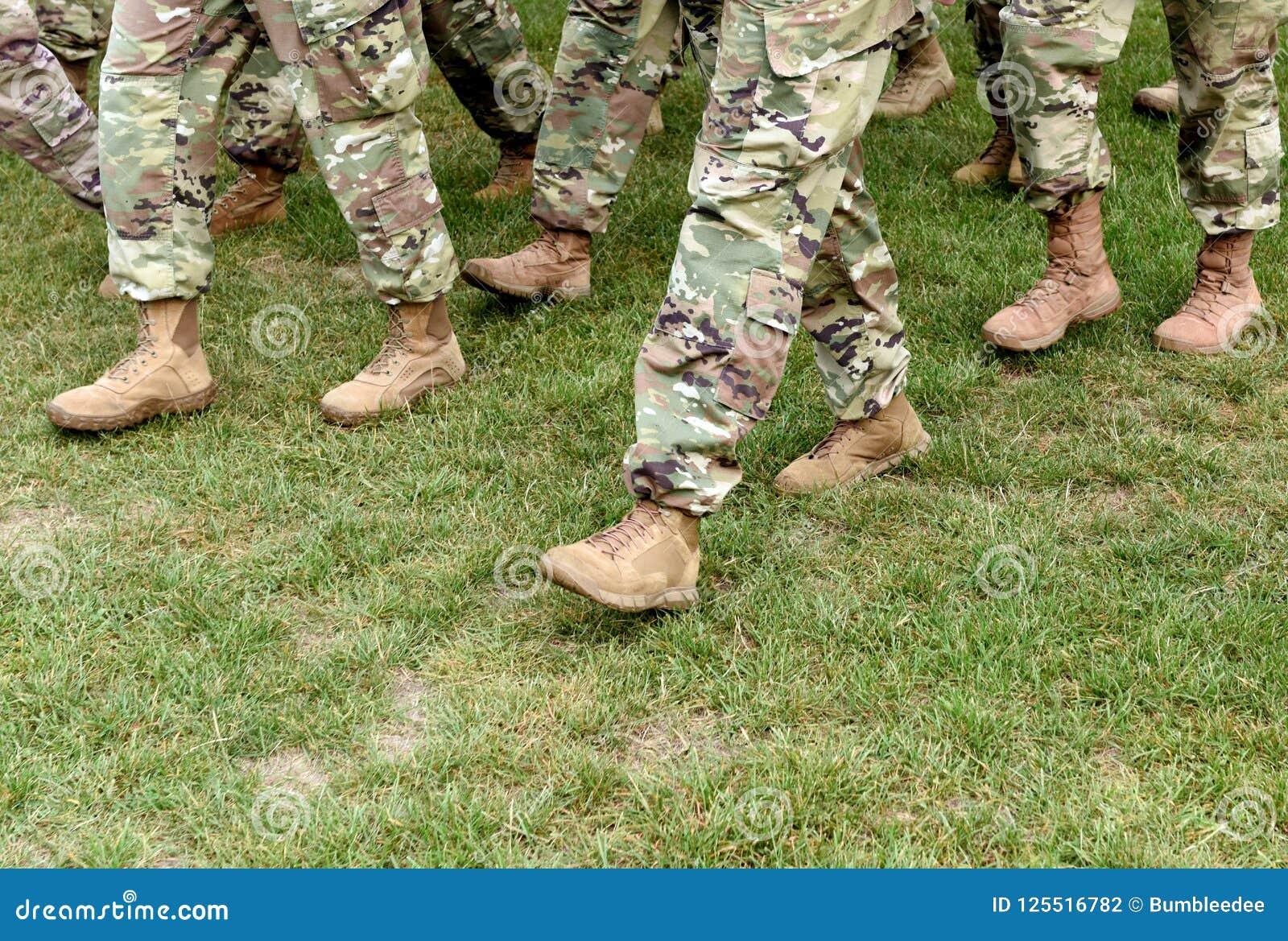 Tropas dos E.U. Soldados que marcham na grama verde Exército dos EUA