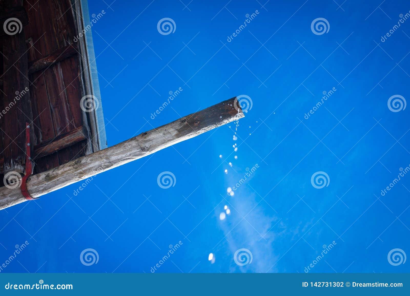 Tropfen, der von einem alten hölzernen Dach fällt
