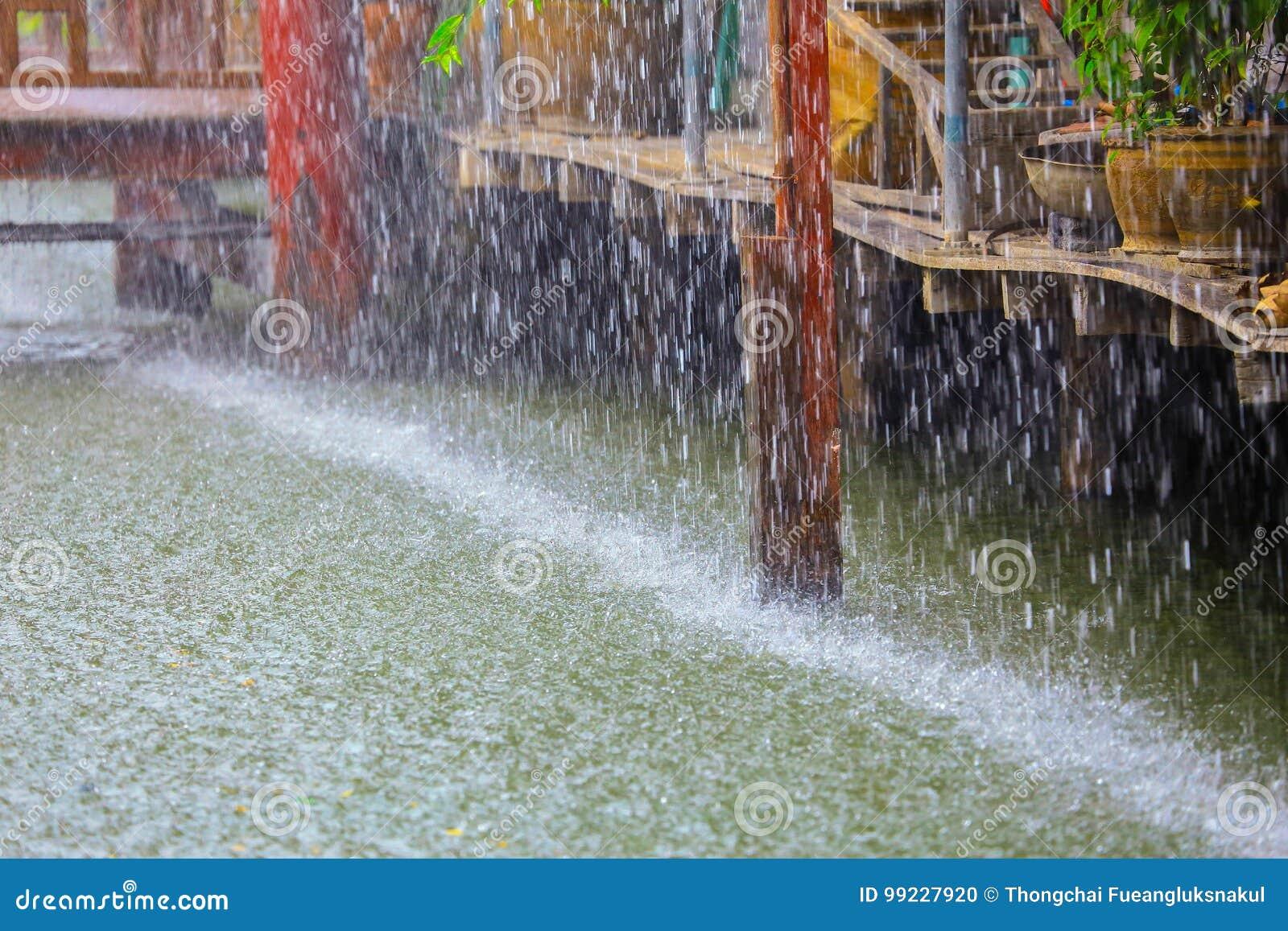 Tropfen des starken Regens des Wassers mit hölzernem Haus der Weinlese auf Kanal
