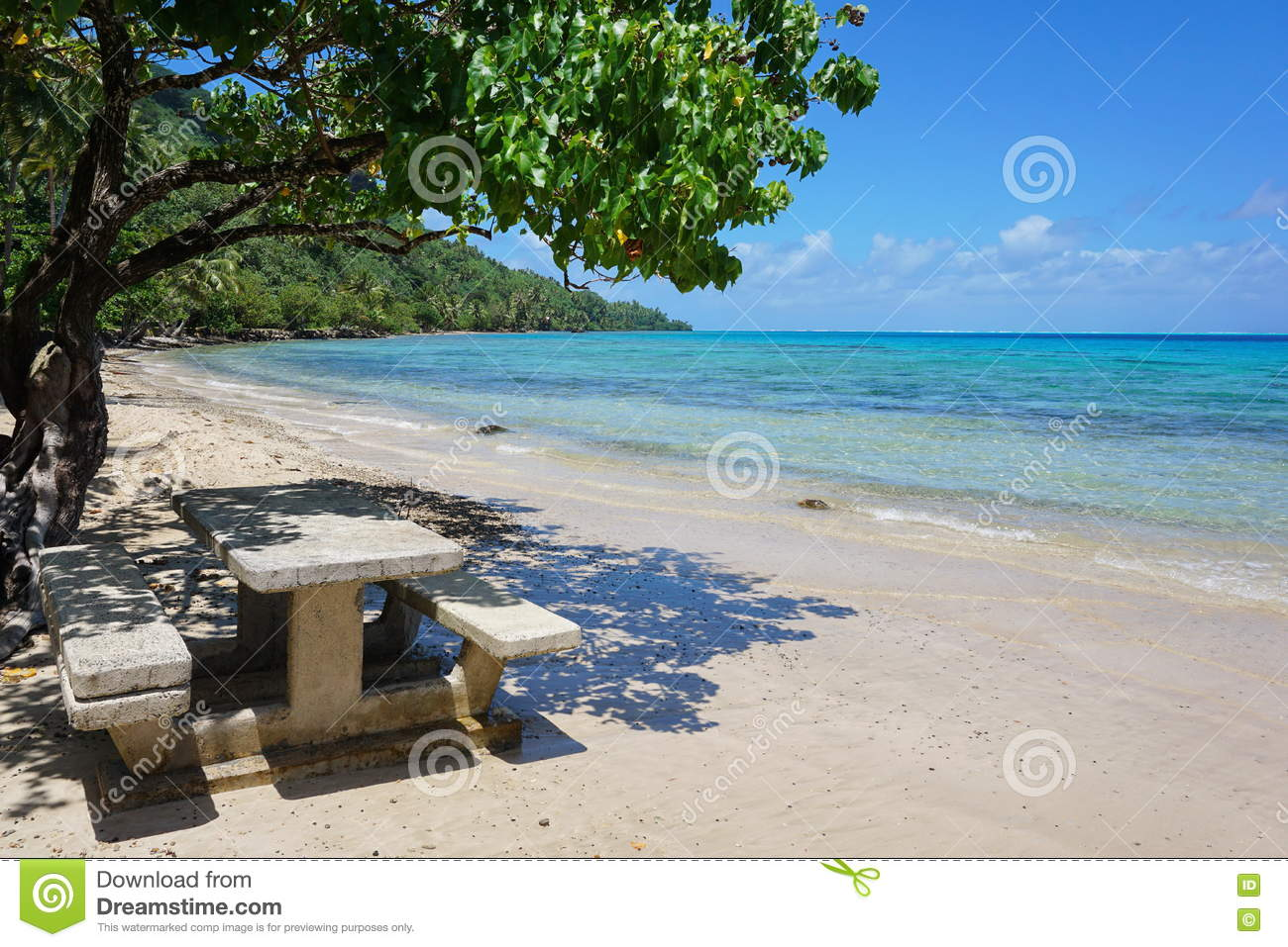 Tropical beach with concrete picnic table on sand