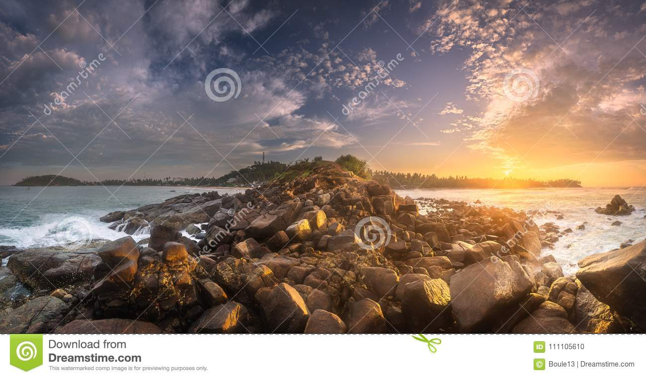 Tropical beach with rocks on sand coast of ocean