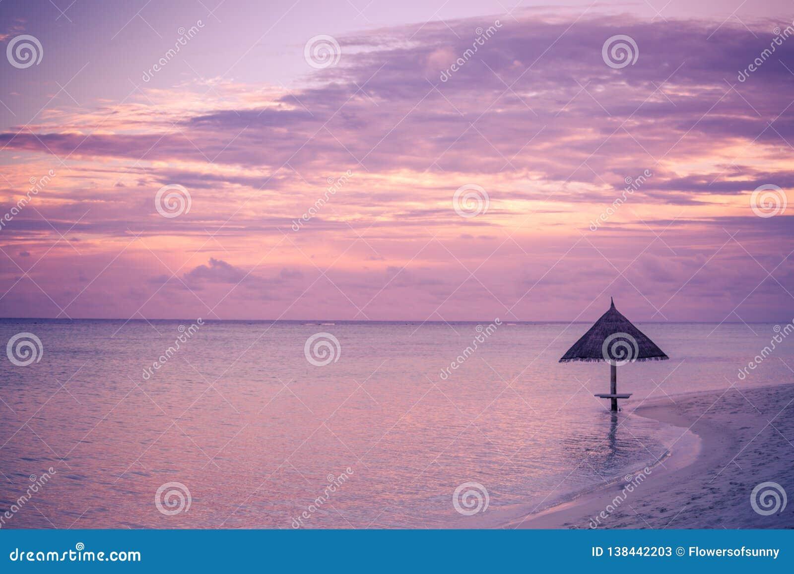 Tropikalny plażowy zmierzch z parasol w Maldives wyspie