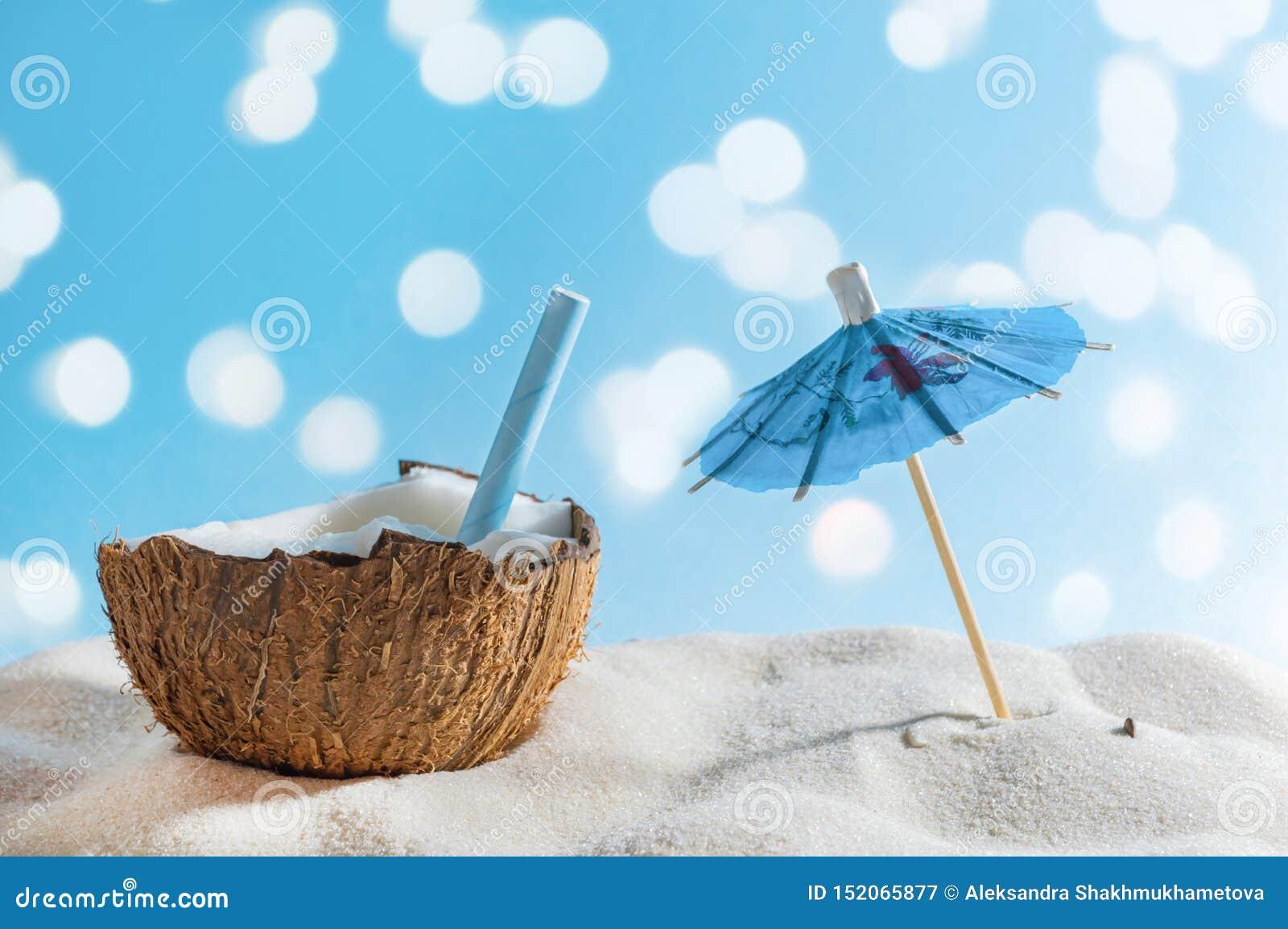 Tropisch strand of reisconcept: de zomercocktail in kokosnoot en zonparaplu