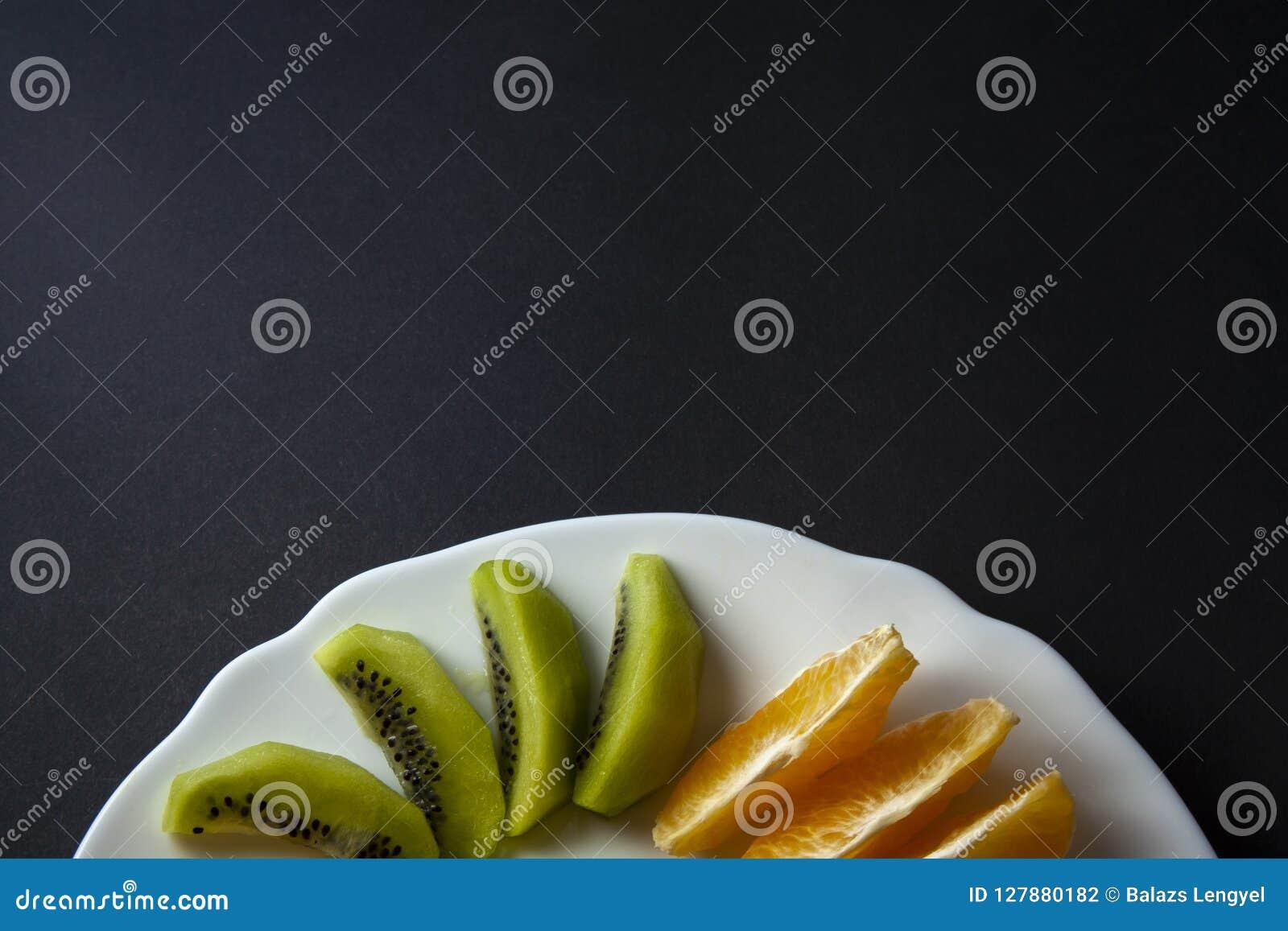 Tropische die vruchten, kiwi en mandarijntjeplakken op wit worden geplaatst