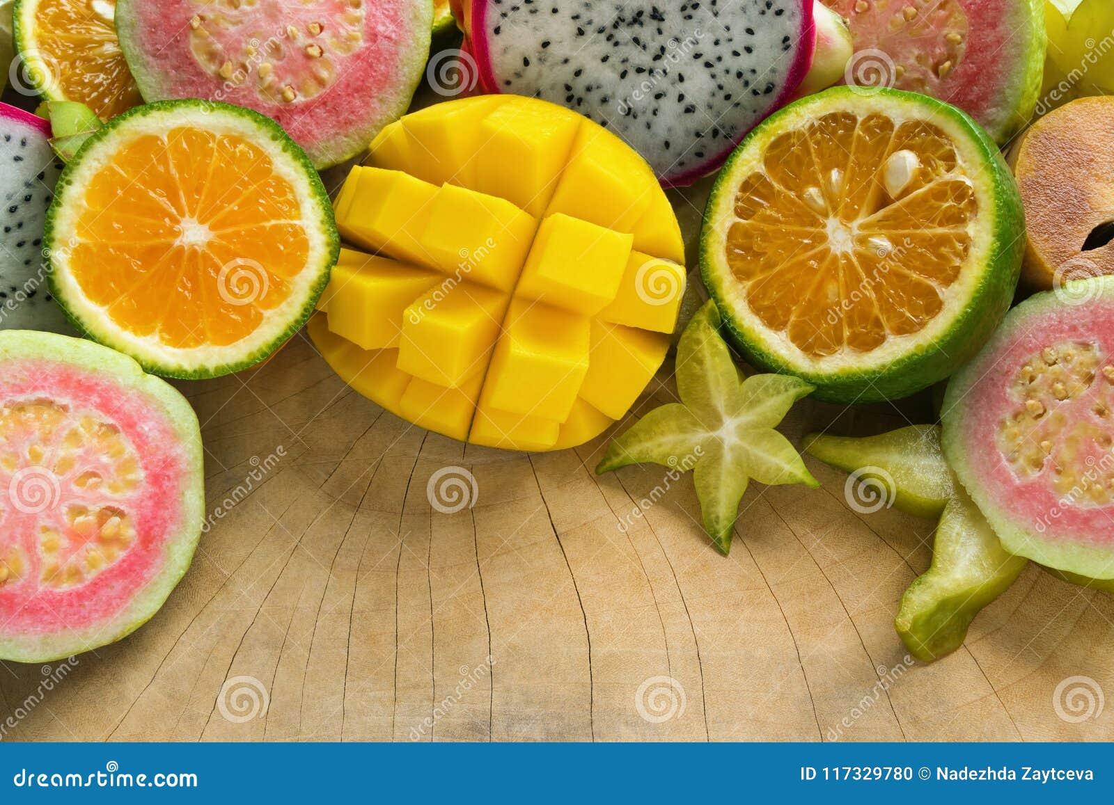 Tropische Früchte Mango, Tangerine, Guave, Drachefrucht, Sternfrucht, Sapotillbaum auf dem hölzernen Hintergrund