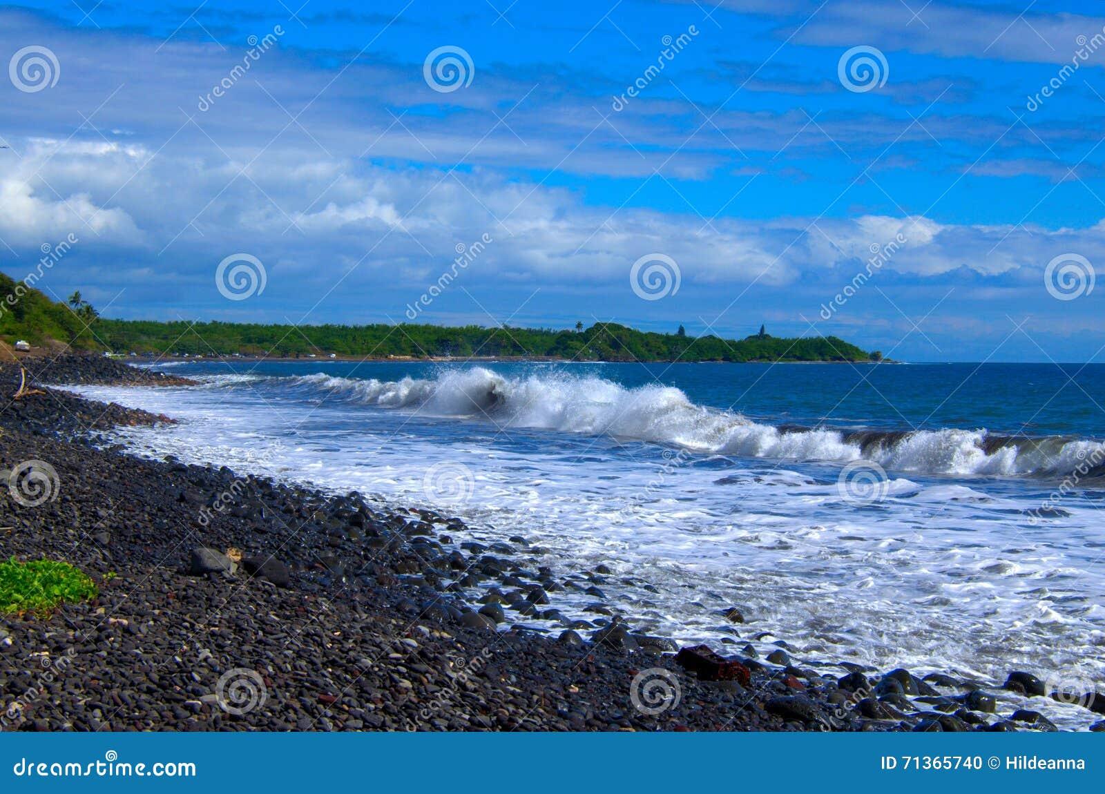 Tropische oceaangolven die op de oever van de lavarots bespatten