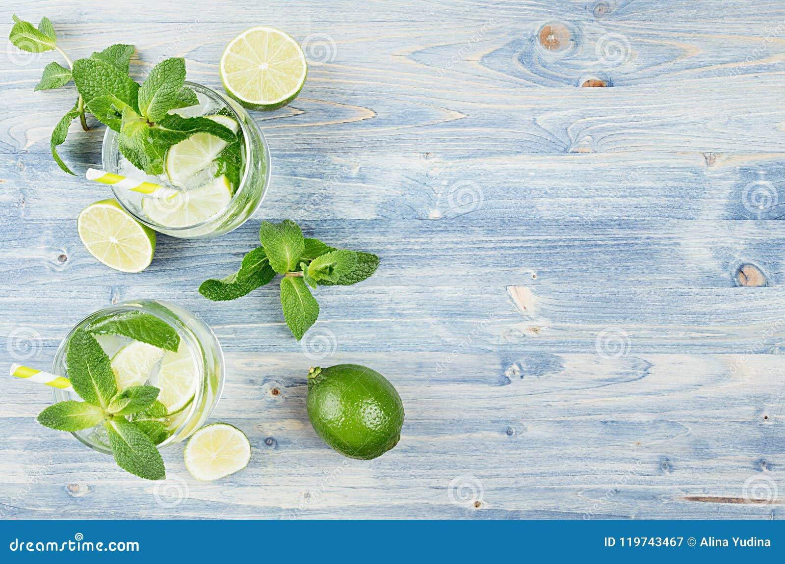Tropisk ny kall coctailginuppiggningsmedel med mintkaramellen, limefrukt, is, sugrör på ljus - blått sjaskigt wood bräde, gräns,