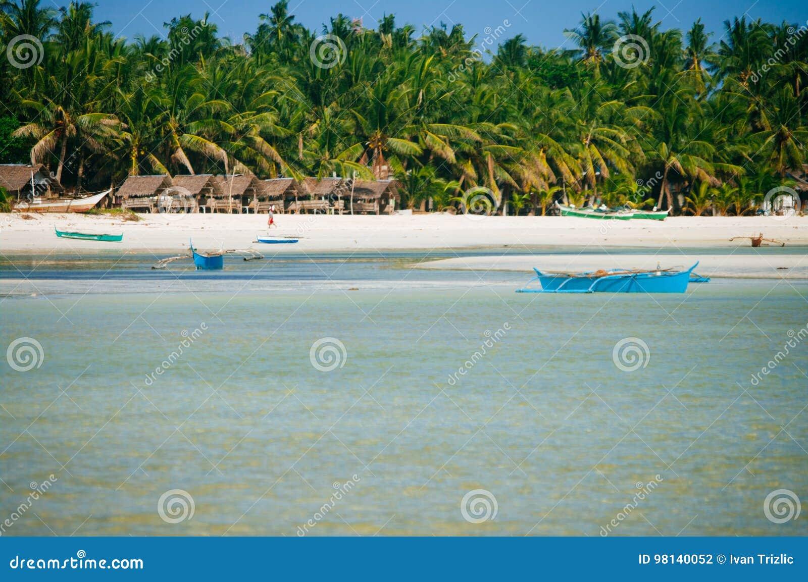 Tropisk vit sandstrand med gröna palmträd och parkerade fiskebåtar i sanden Exotiskt öparadis